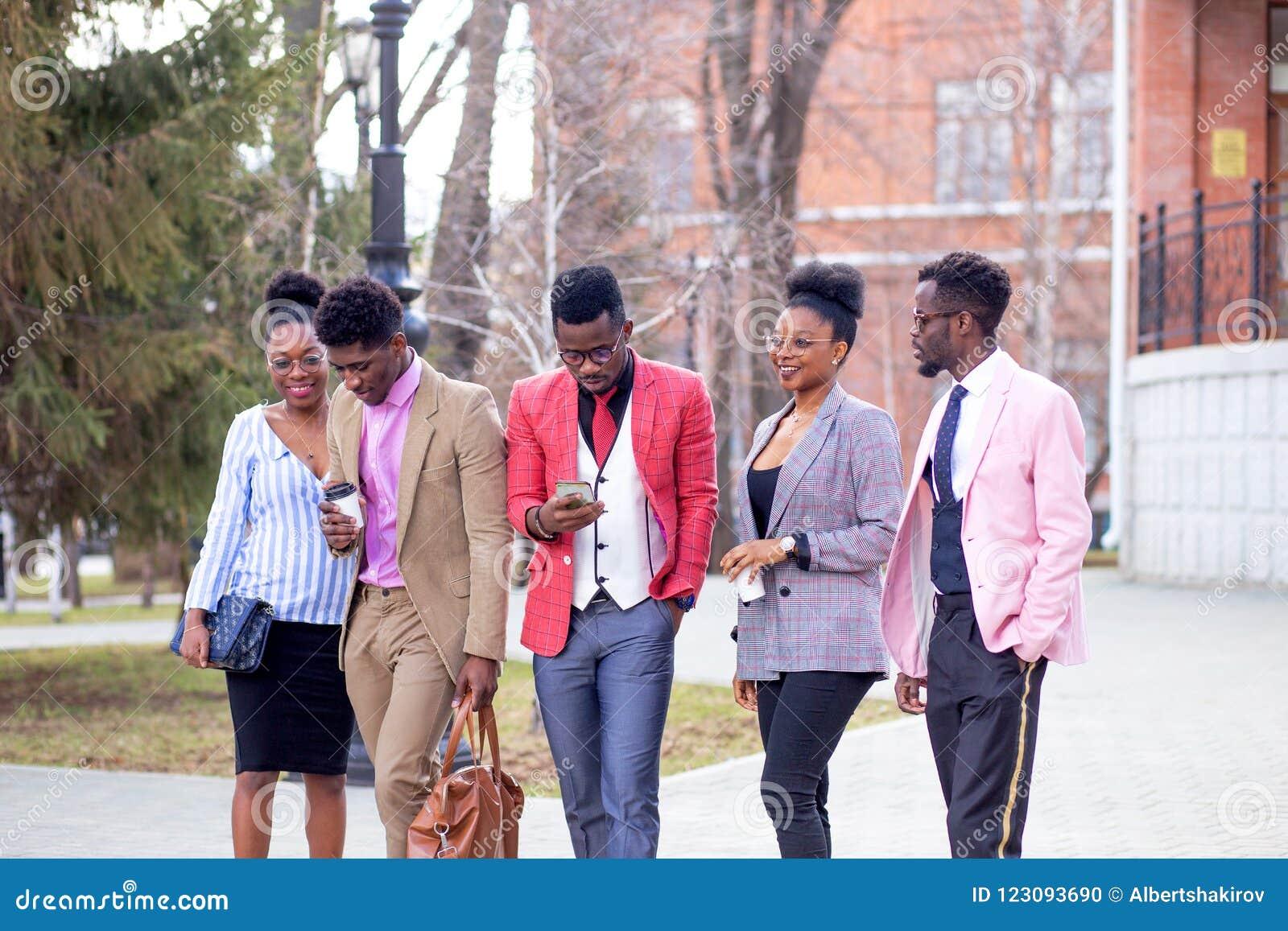 Ocio y concepto adolescente un grupo de amigos felices que dan un paseo en la calle