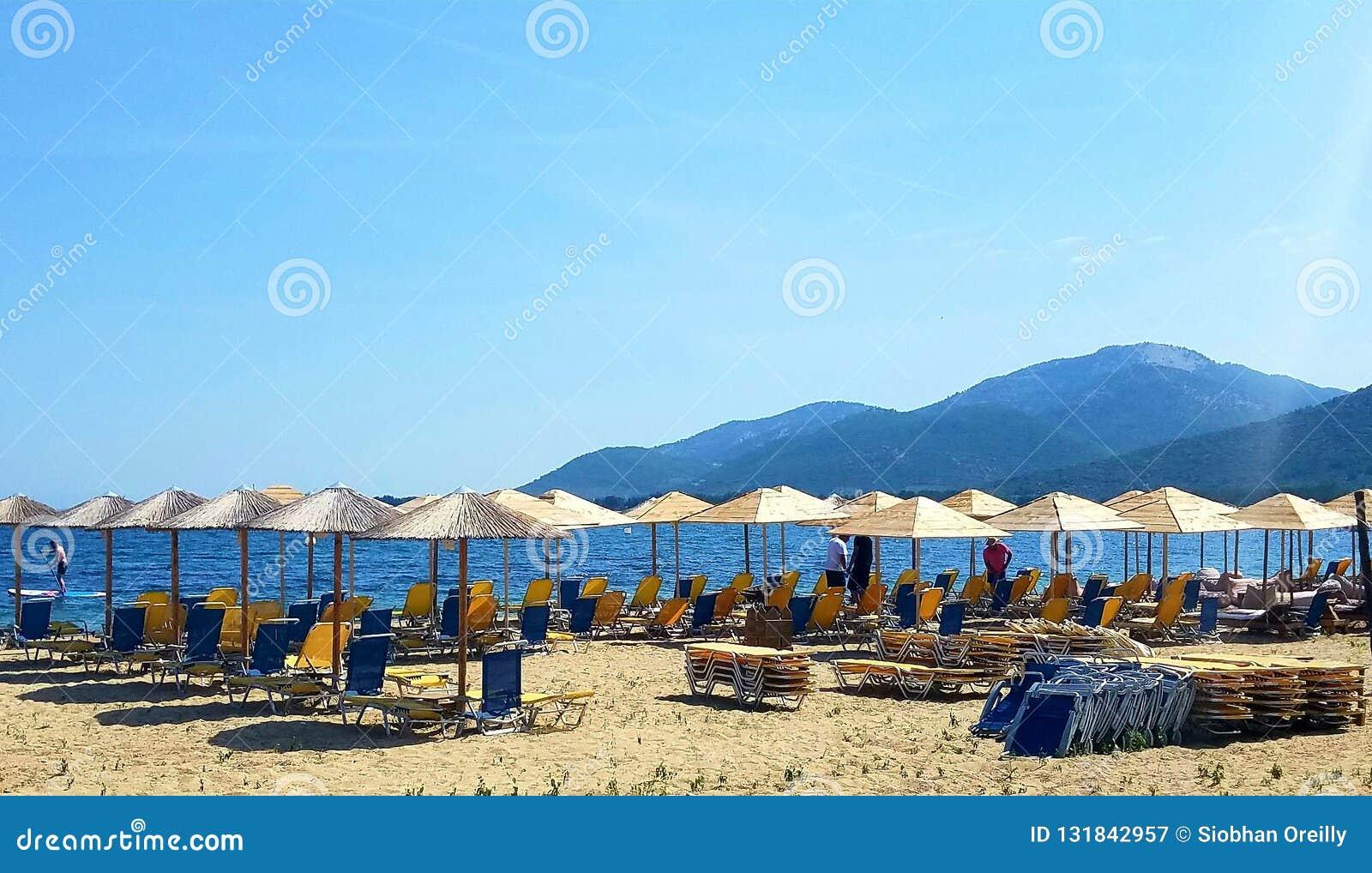 Ociosos y paraguas de Sun que esperan fabricantes del día de fiesta en una playa en Grecia