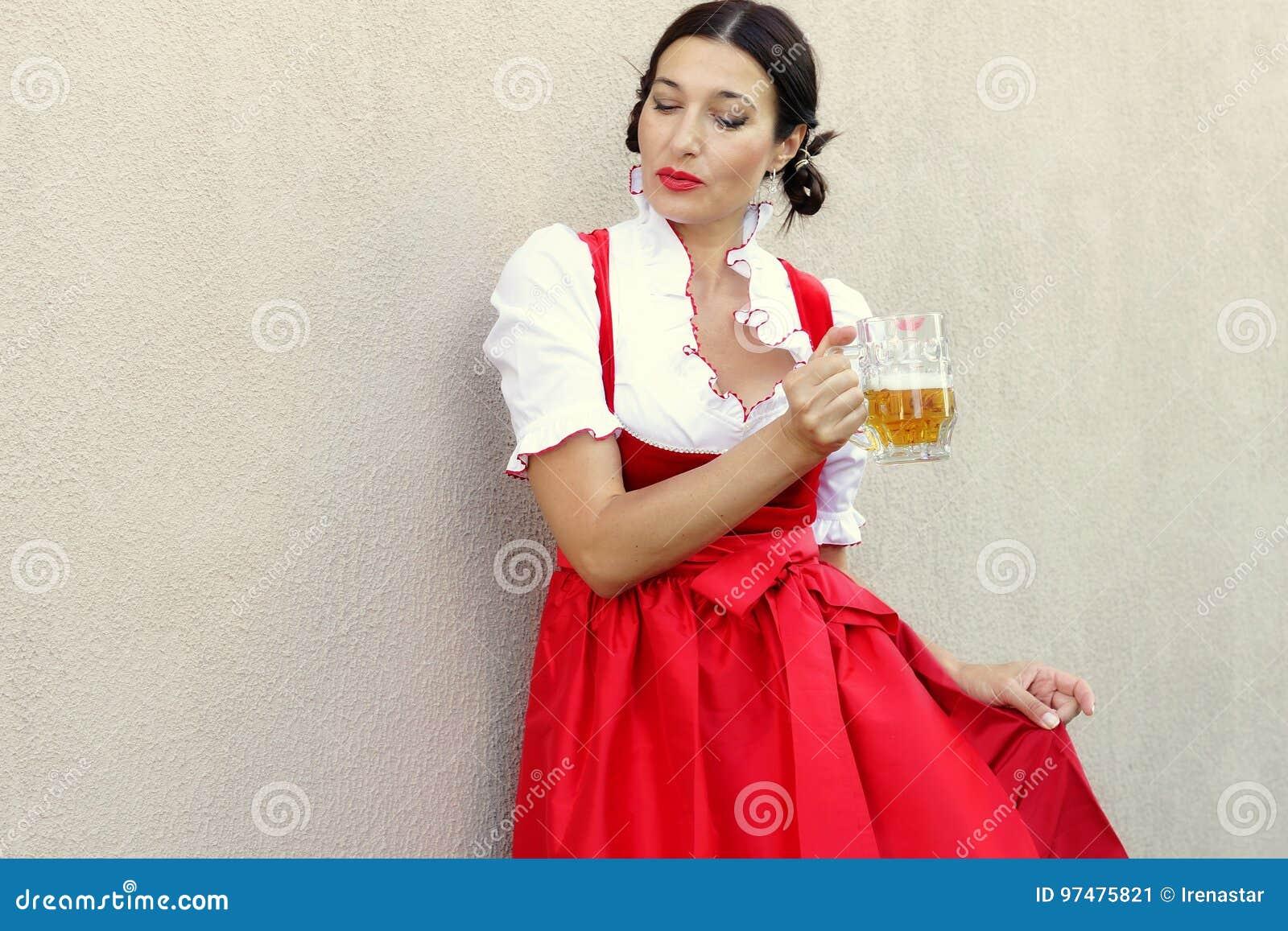October fest concept.Beautiful german woman in typical oktoberfest dress dirndl holding a glass beer mug