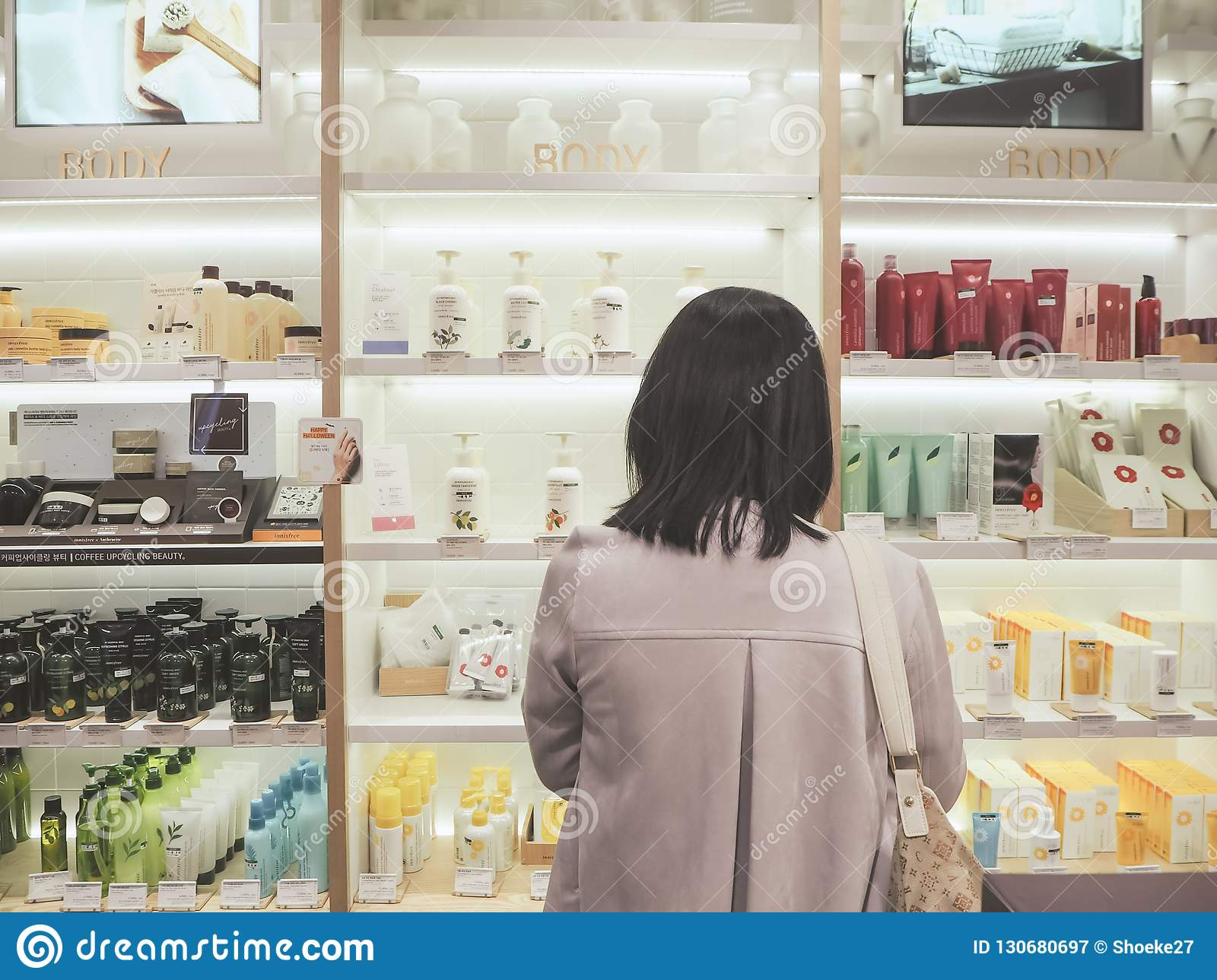 Young Asian woman standing in front of a shelf with skincare products