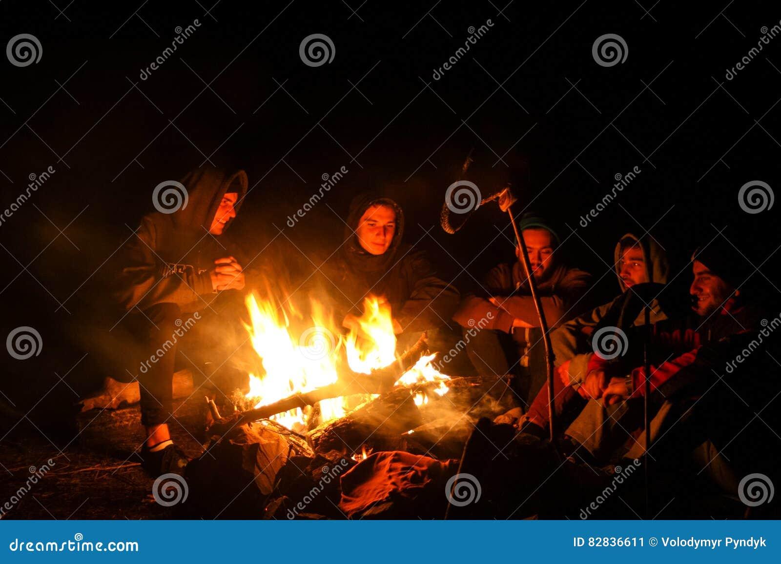 Octobre 2014 : groupe d amis riant et s asseyant au feu de camp après longue hausse de montagne d automne