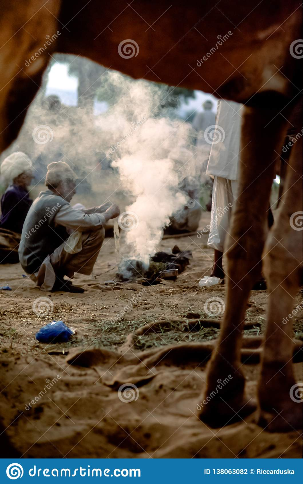 Ocupa dos comerciantes do camelo em torno das brasas de um fogo no crepúsculo, Pushkar Mela, Rajasthan, Índia