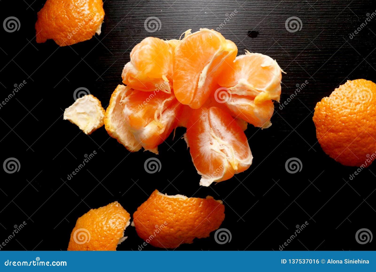 Oczyszczony tangerine na czarnym tle Pożytecznie cytrus