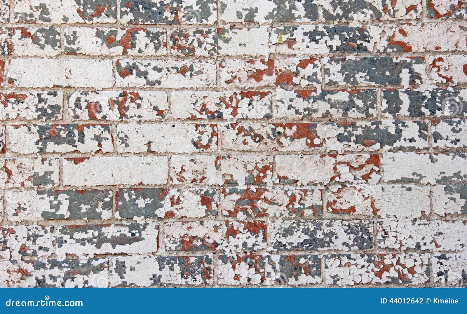 Odłupany czerwony biały błękitny farby ściana z cegieł