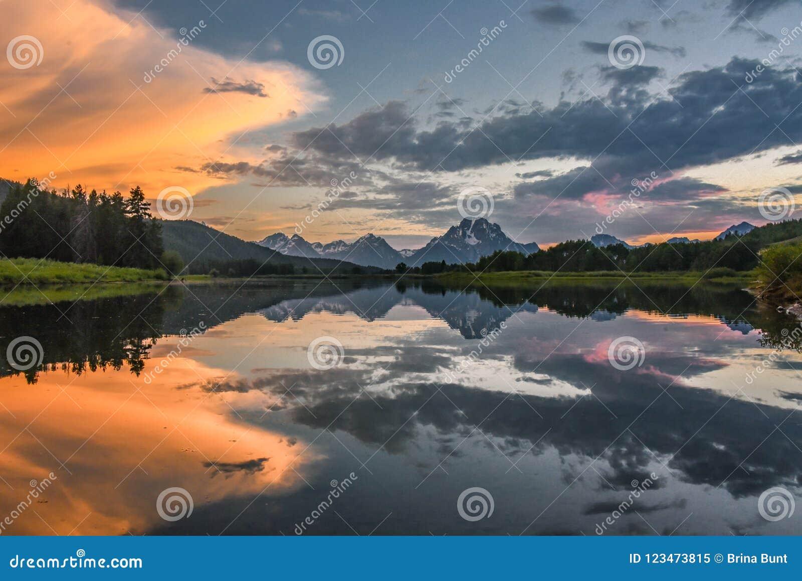 Odbicie Uroczysty Tetons w Jackson jeziorze przy zmierzchem z pięknymi chmurami