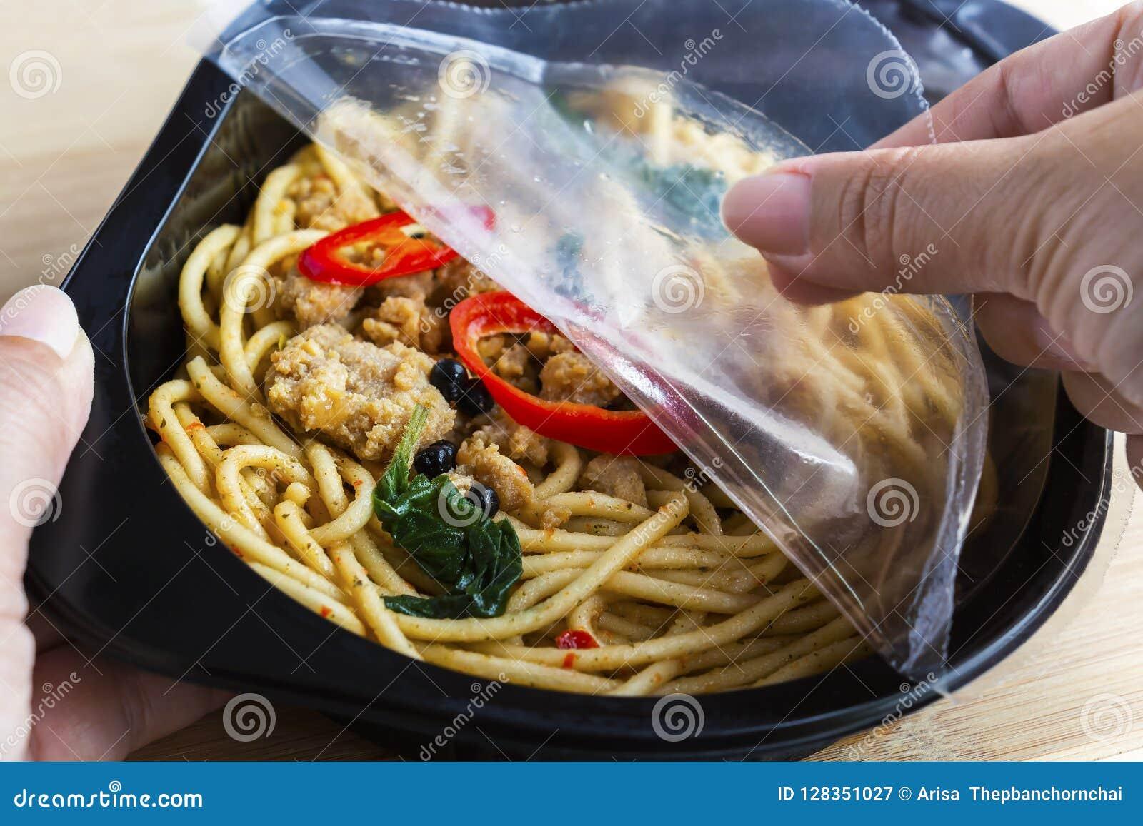 Oddalony karmowy przygotowywający posiłek: Kobiet ręki trzyma otwartymi przylegają opakunek a