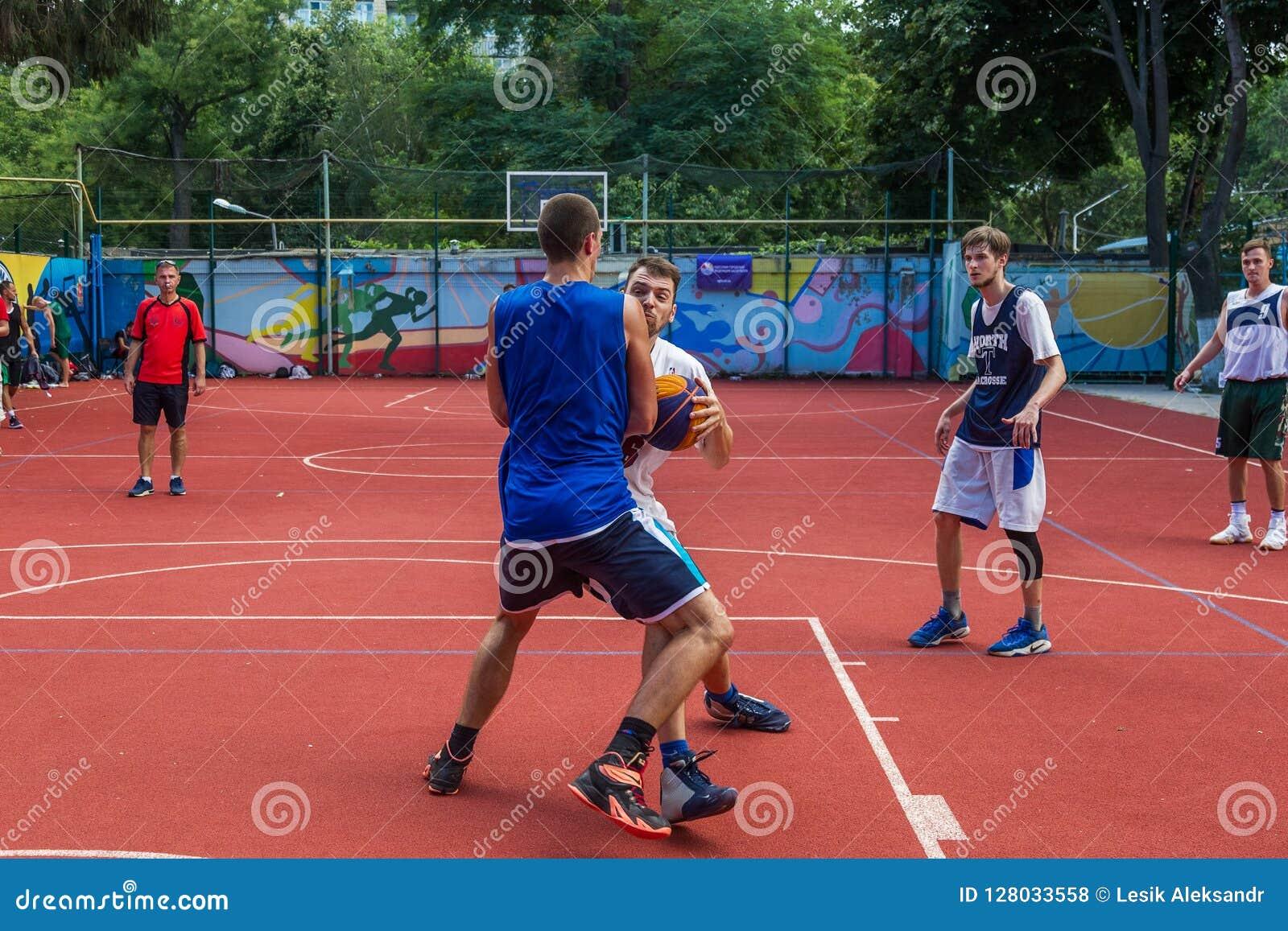 ODESSA UKRAINA - JULI 28, 2018: Tonåringlekbasket under mästerskap för streetball 3x3 Basketba för gata för ungdomarlek