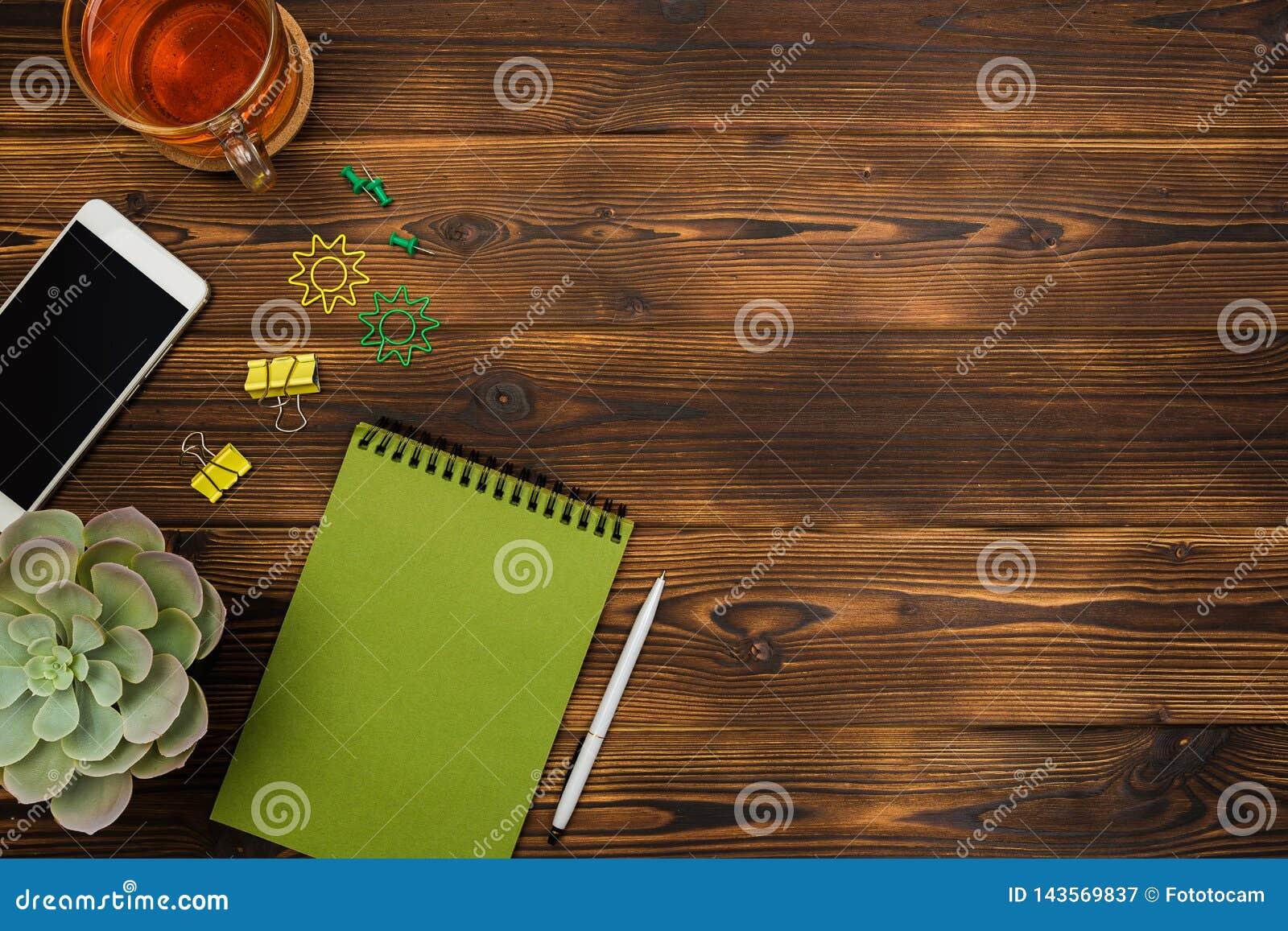 Odgórnego widoku biznesu biurowy biurko notatnik, ołówek, herbaciana filiżanka, roślina, telefon komórkowy, paperclips na drewnia