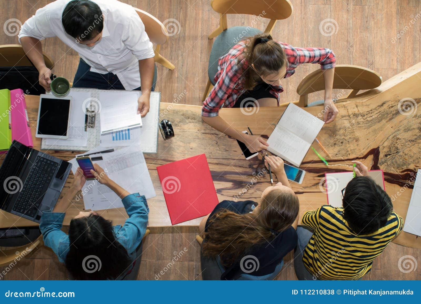 Odgórnego widoku grupa nastoletni przyjaciele być ruchliwie działaniem w drużynie z raportami i laptopie przy uniwersytetem