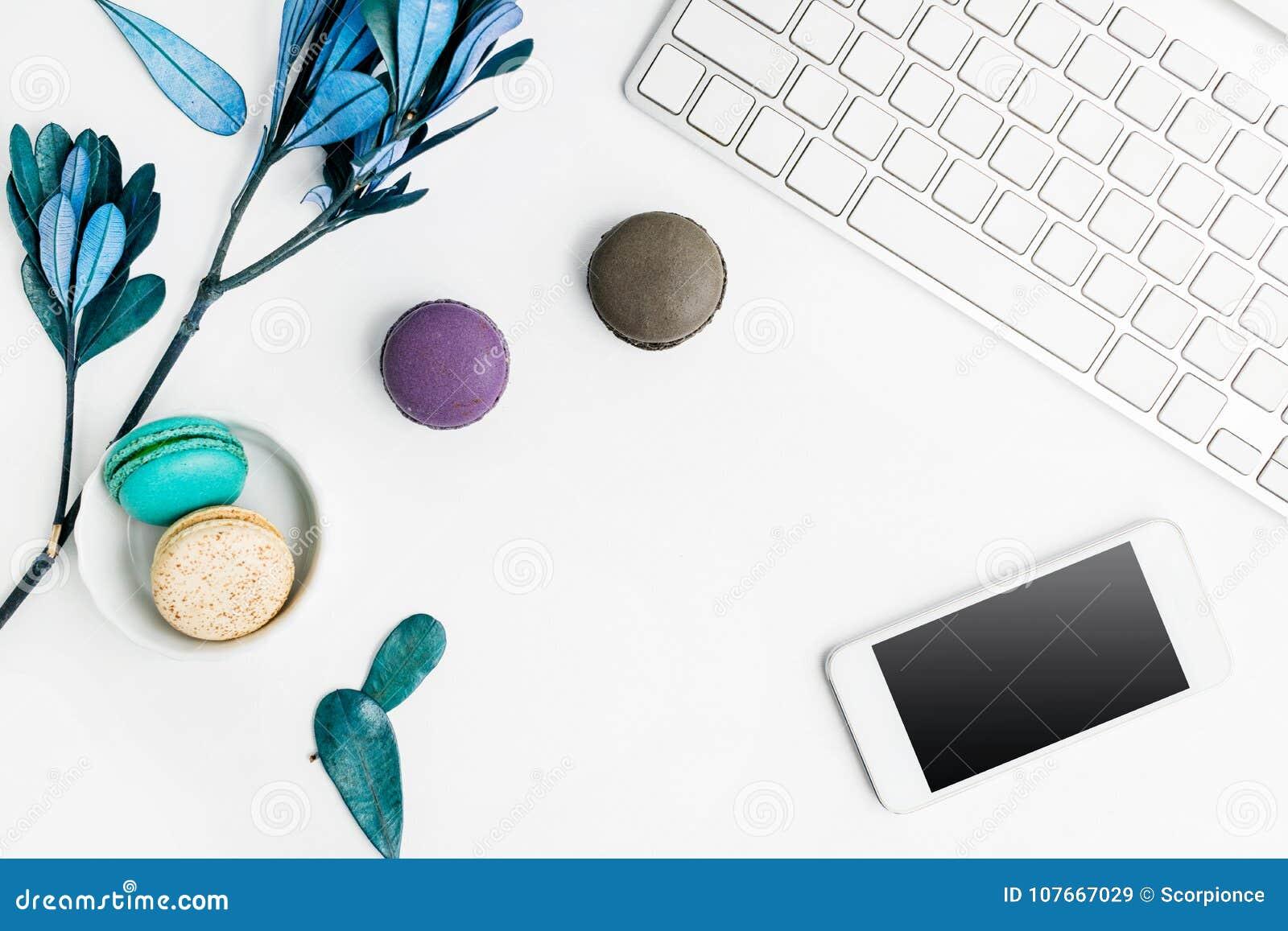 Odgórnego widoku mieszkania nieatutowi kolorowi macarons z klawiatury, telefonu komórkowego i błękita liśćmi na bielu stole, Krea