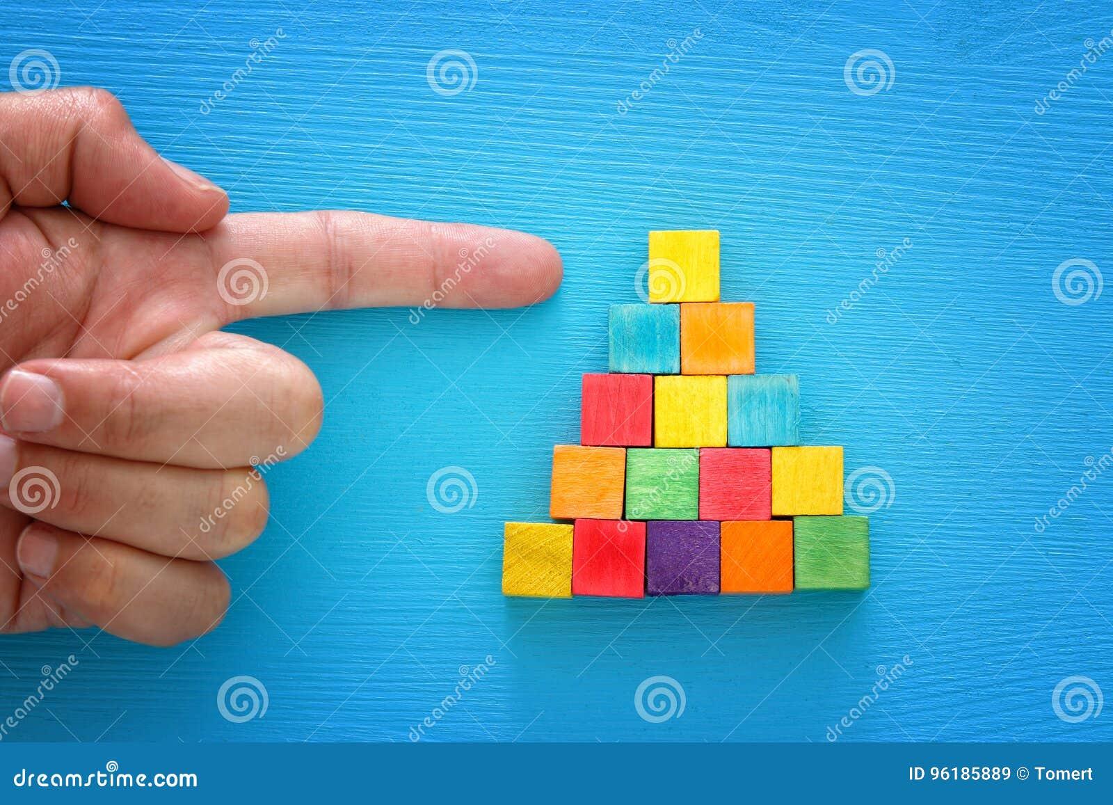Odgórnego widoku wizerunek męska ręka wskazuje wierzchołek drewnianych bloków ostrosłup