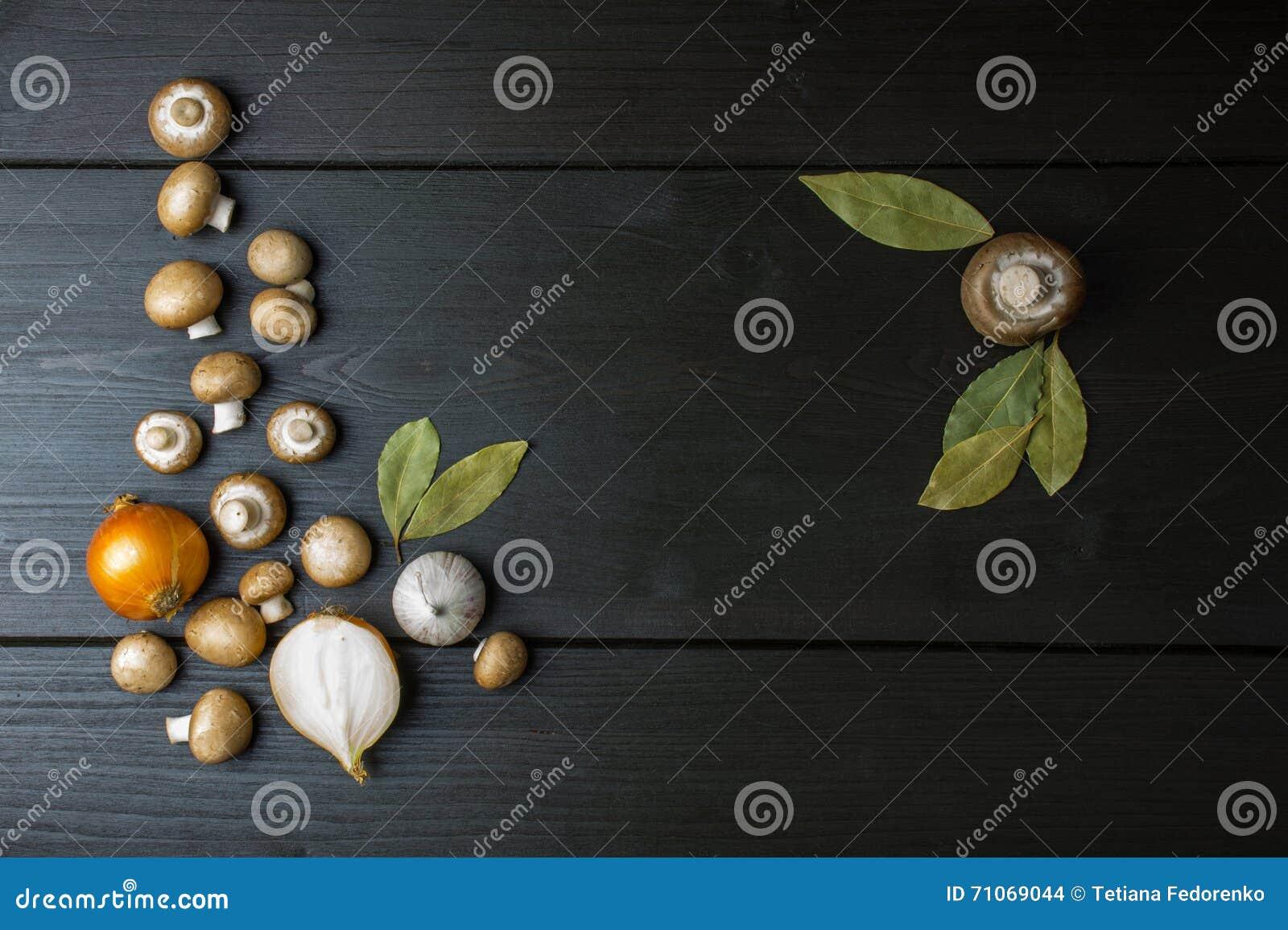 Odgórny widok świeże pieczarki i cebula z podpalanym liściem na zmroku wo