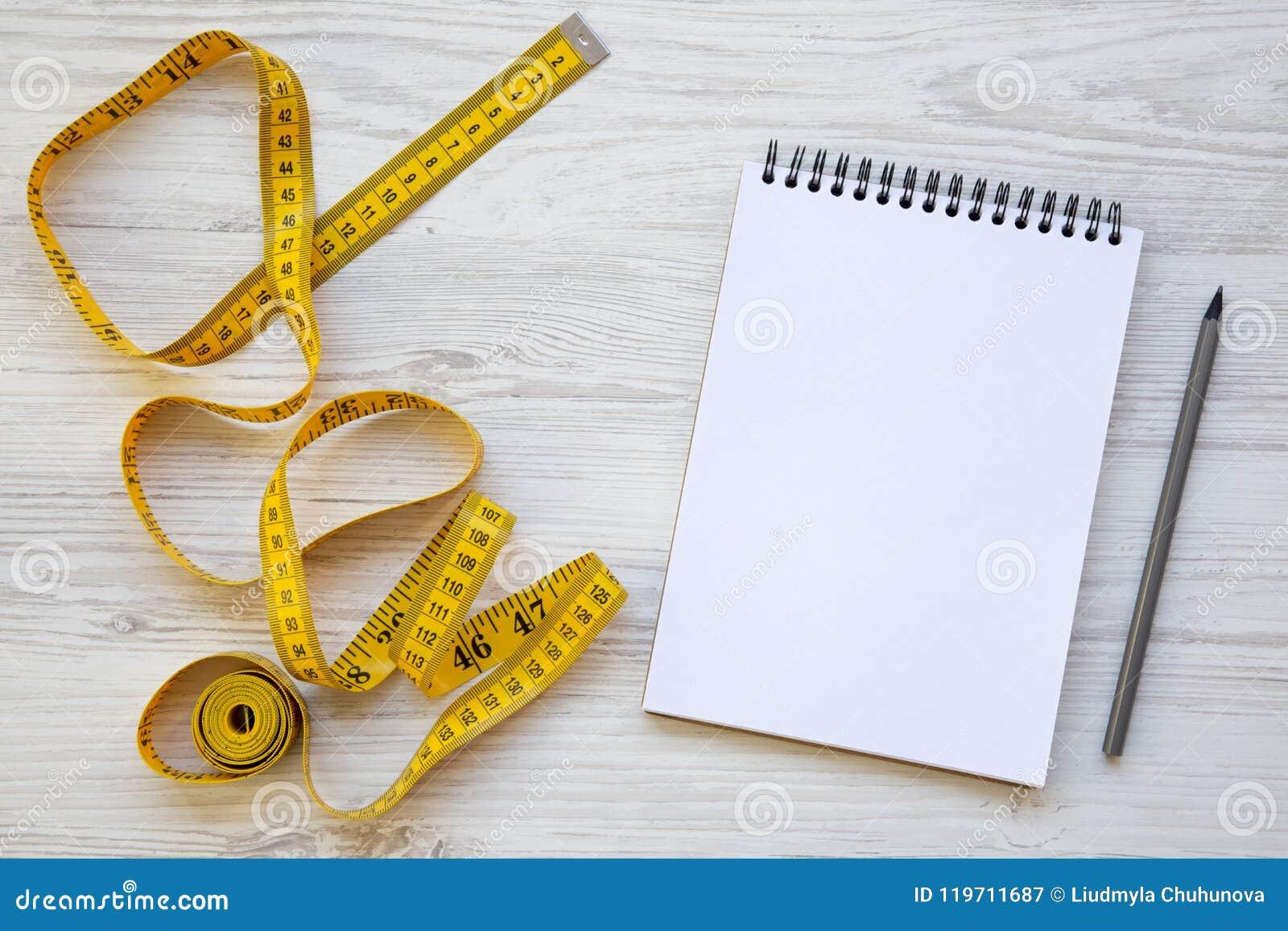 Odgórny widok, żółta pomiarowa taśma z notepad i ołówek na białym drewnianym stole,