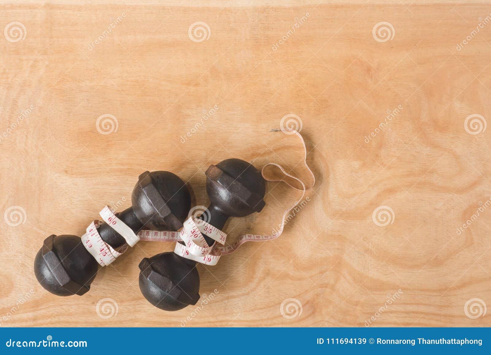 Odgórny widok żelazni dumbbells z miarą taśmy na drewnianym stole