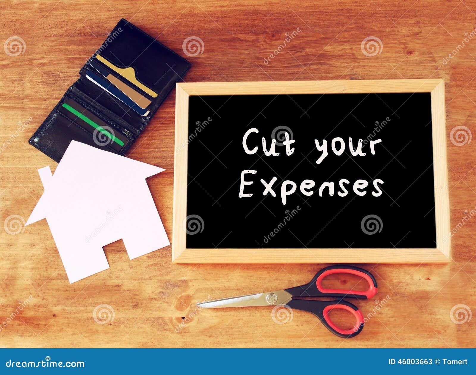 Odgórny widok blackboard z sloganem ciie twój kosztów nożyce, portfel z kredytowymi kartami i dom kształtującego papier, gospodar