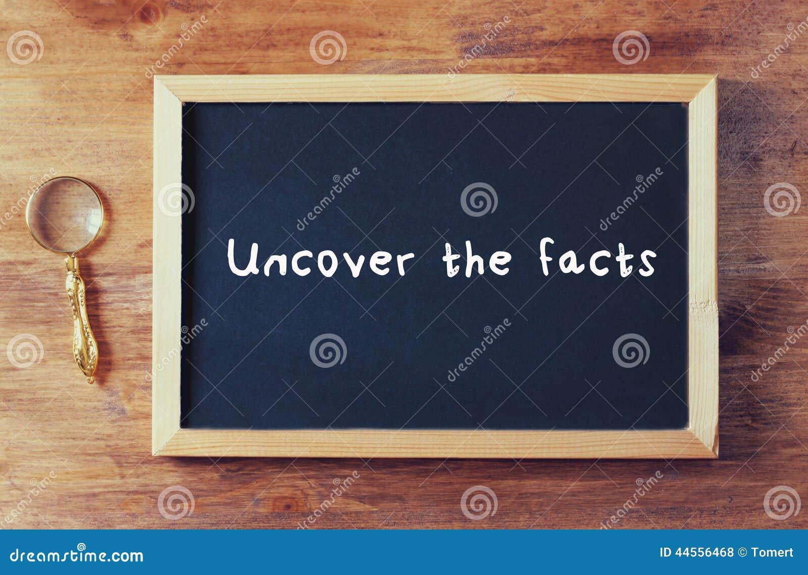 Odgórny widok blackboard z zwrotem odkrywa fact pisać na nim obok stary powiększać - szkło nad drewnianym stołem