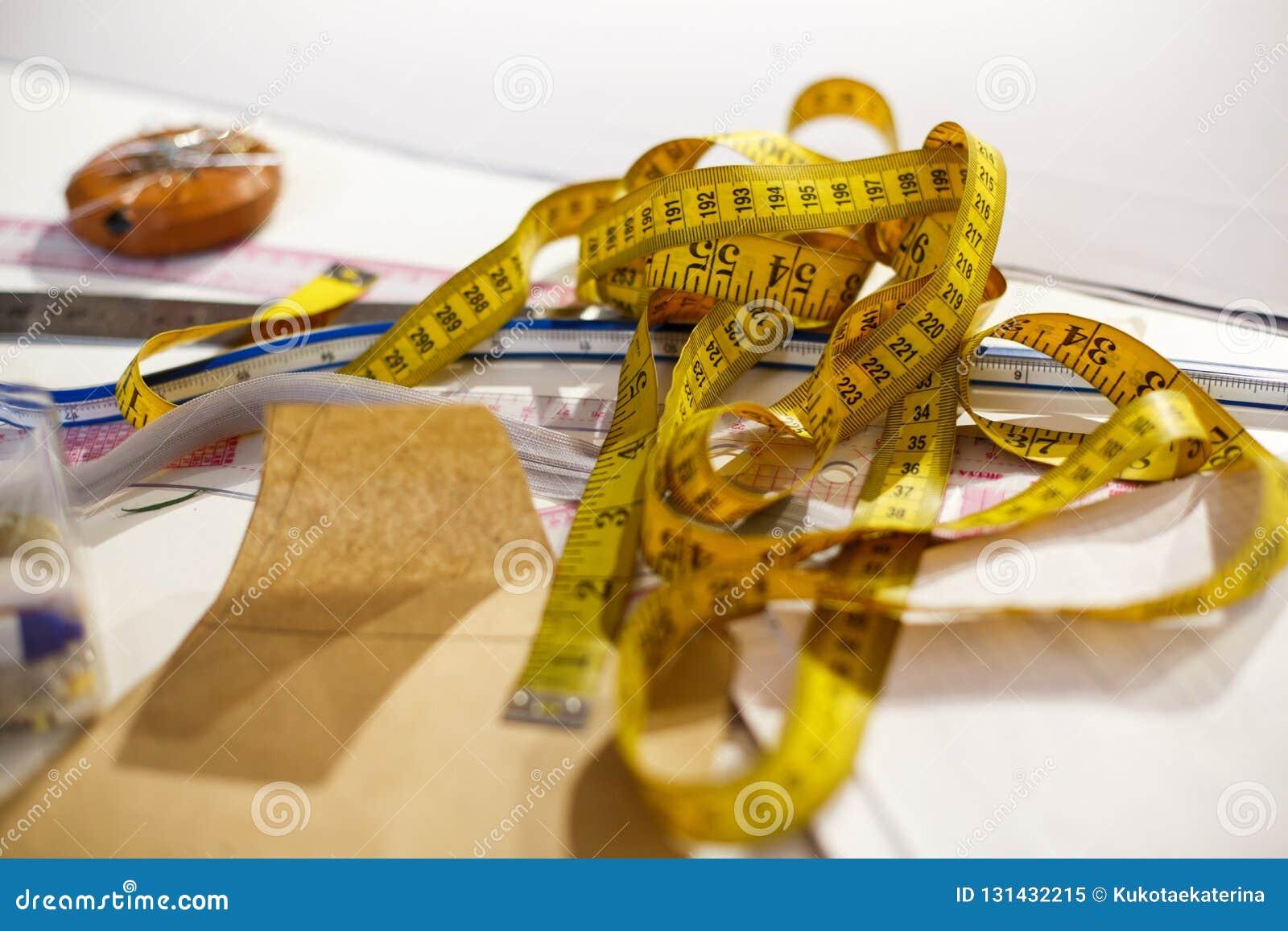 Odgórny widok centymetrowy kolor żółty, nożyce, władca i inni narzędzia szwaczka, Robić odziewa Miejsce pracy krawczyna