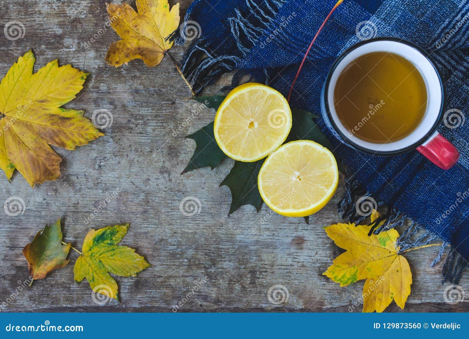 Odgórny widok filiżanka herbata, błękitny szalik, pokrojona cytryna i liście na drewnianym tle,