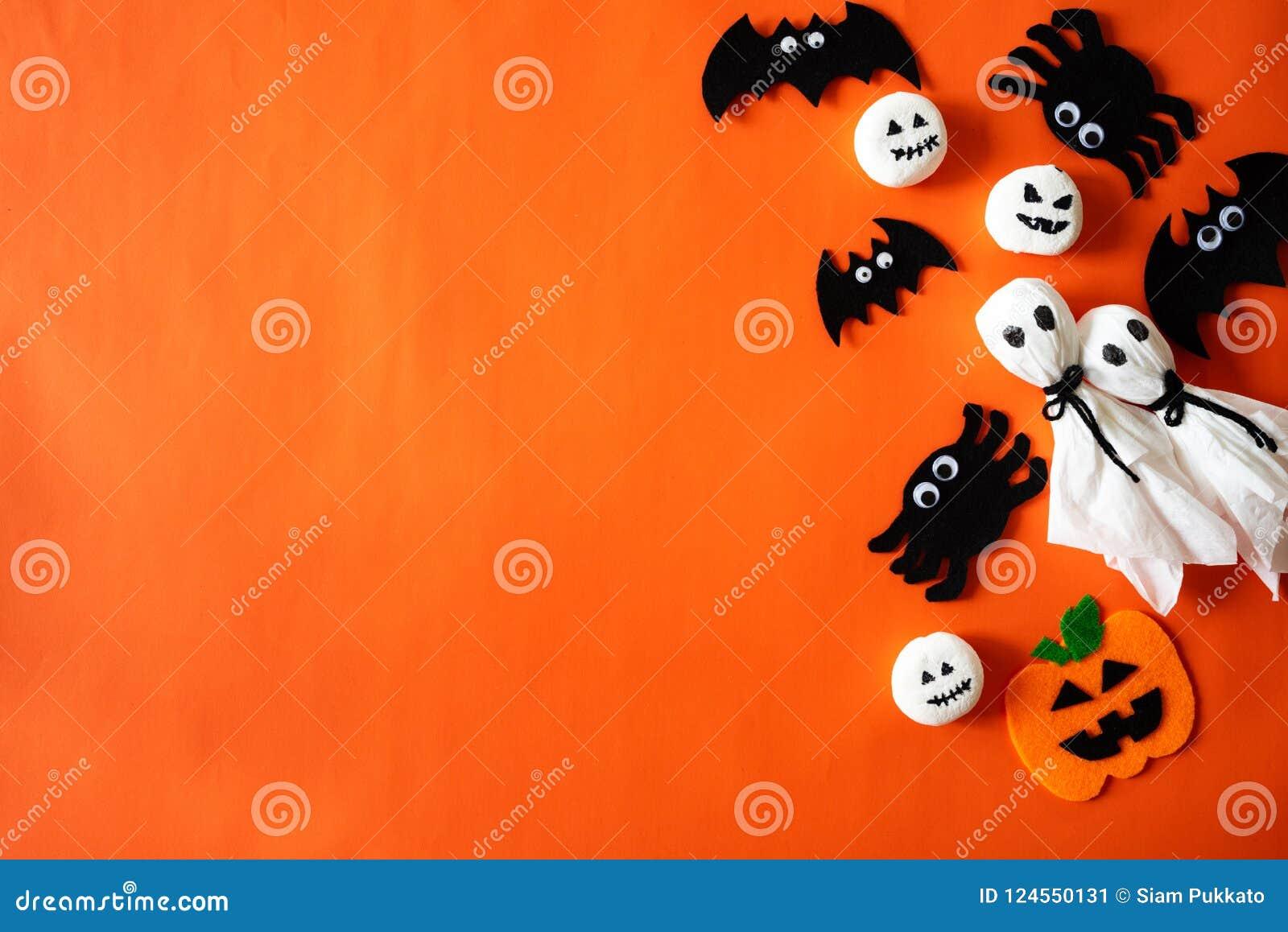 Odgórny widok Halloweenowi rzemiosła, pomarańczowa bania, duch i pająk na pomarańczowym tle,