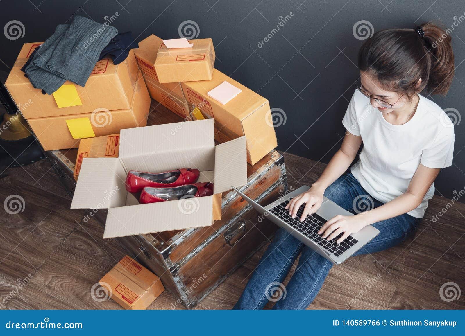 Odgórny widok kobiety pracuje laptop od domu na drewnianej podłoga z pocztowym pakuneczkiem, Sprzedaje online pomysłu pojęcie