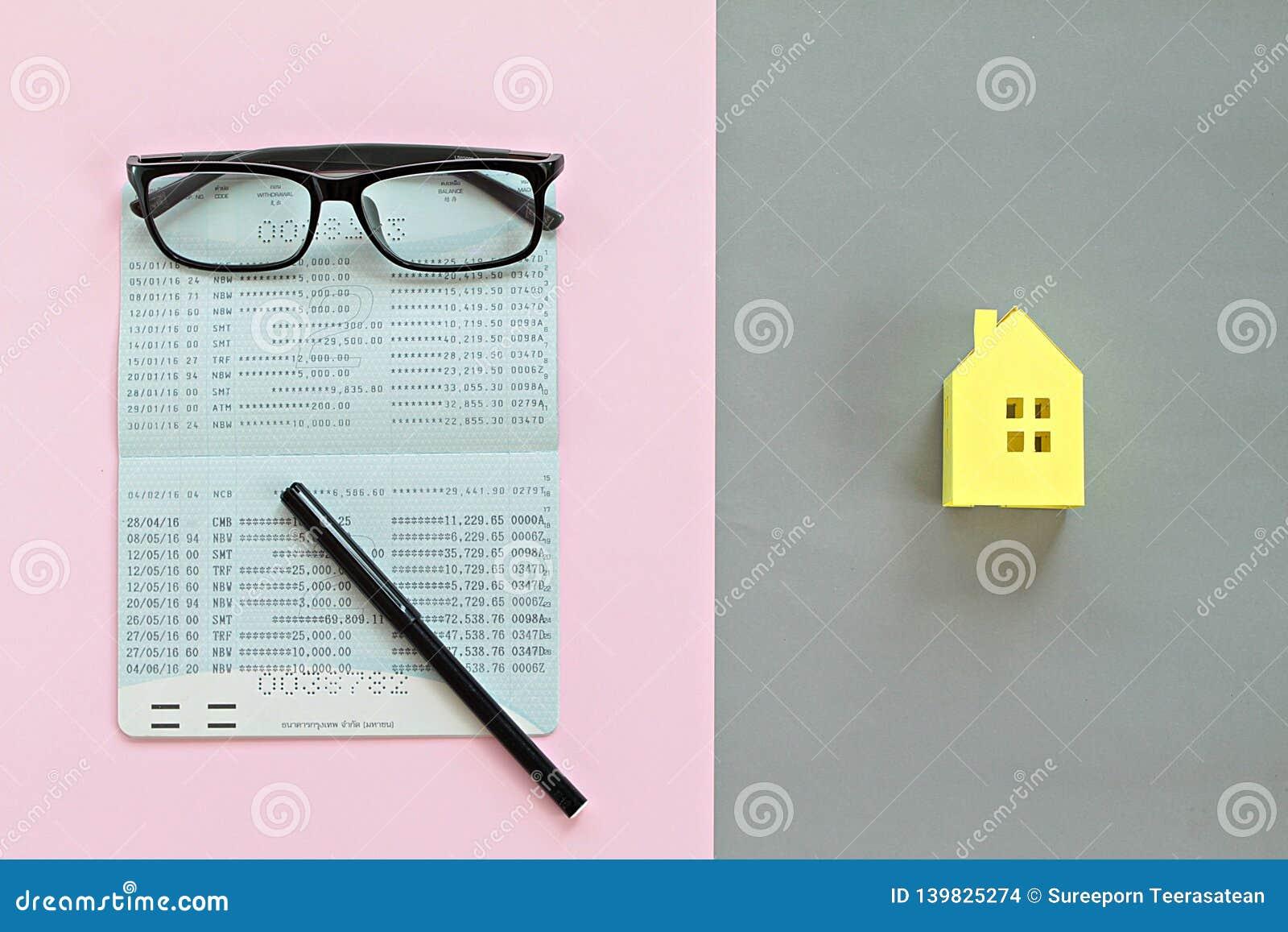 Odgórny widok lub mieszkanie nieatutowi oszczędzania obrachunkowy passbook i koloru żółtego papieru dom modelujemy na tle