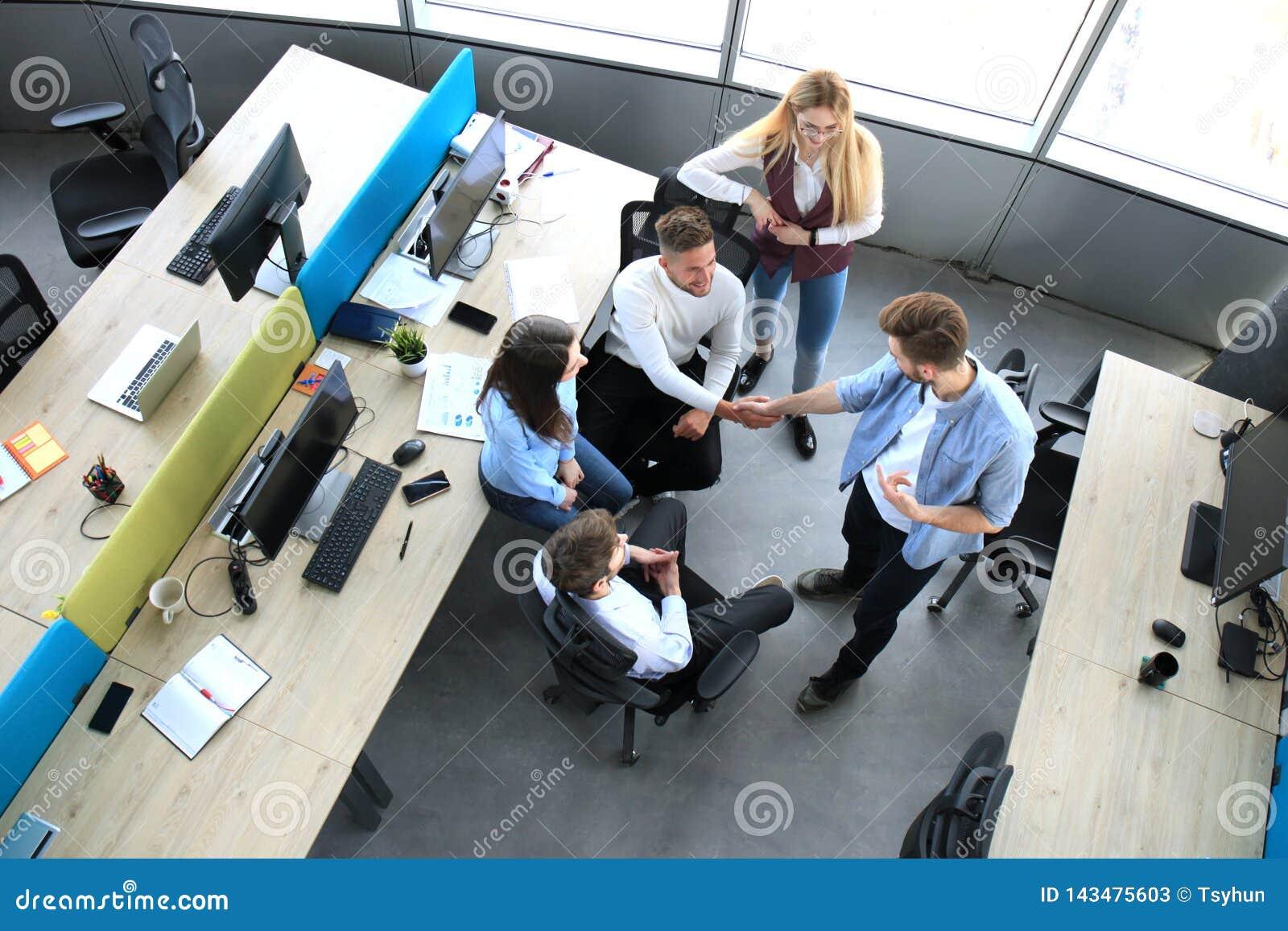 Odgórny widok młodzi partnery biznesowi trząść ręki nad transakcją przy biurem Ostrość na ręki potrząśnięciu