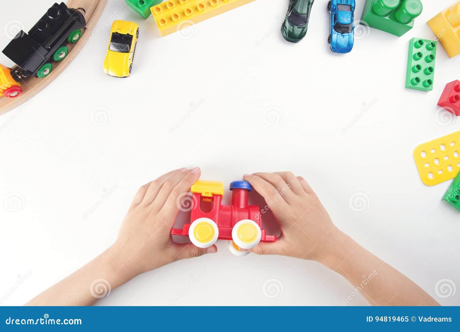 Odgórny widok na dziecka ` s rękach bawić się z zabawka pociągiem i wiele zabawkami na białym stołowym tle
