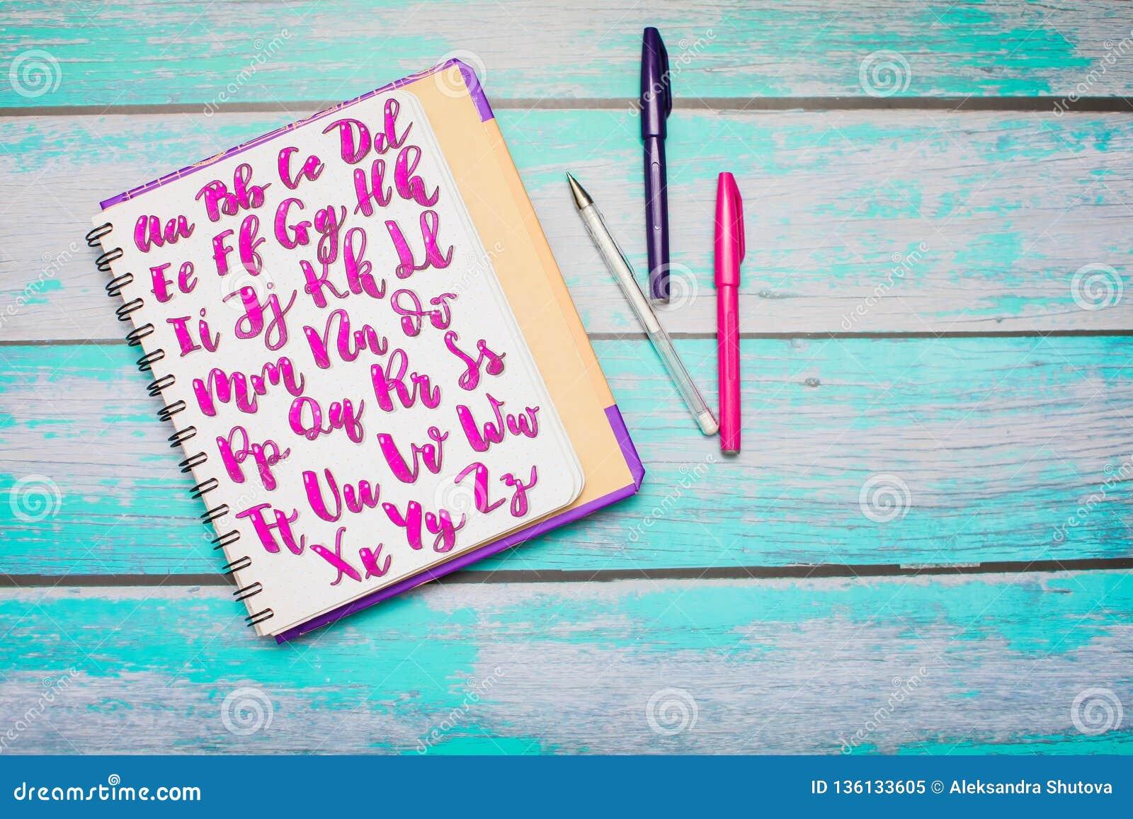 Odgórny widok notatnik z ręka rysującymi abc abecadła listami i kolorowymi piórami na błękitnym drewnianym biurka tle