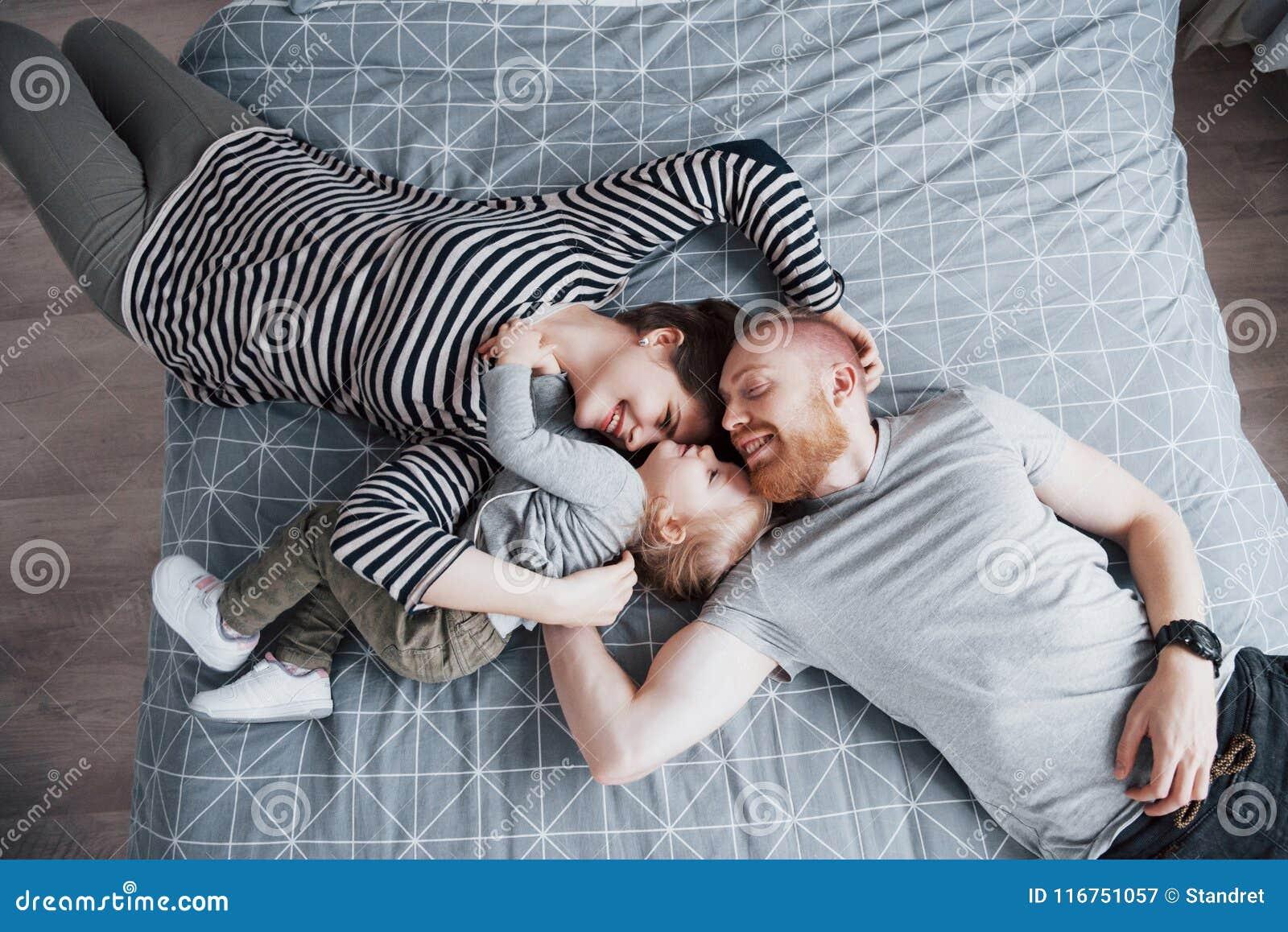 Odgórny widok piękni potomstwa matkuje, ojciec, ich córka i podczas gdy kłamający na łóżko głowie patrzeje kamerę i ono uśmiecha