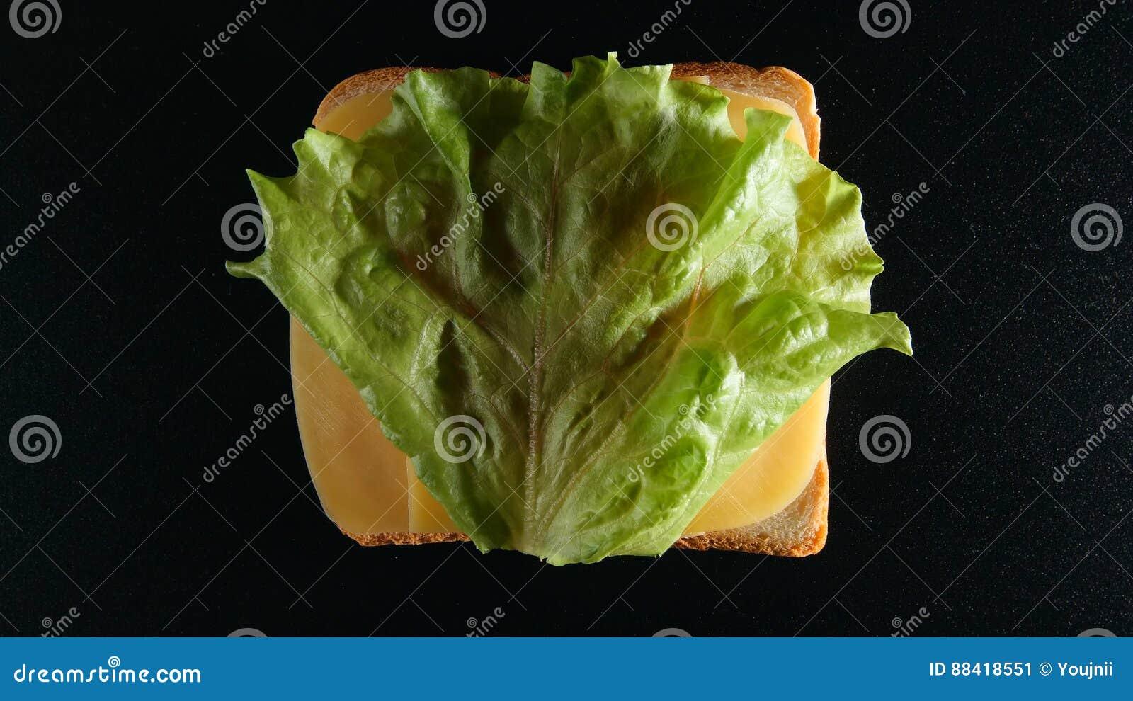 ODGÓRNY widok: Plasterek chleb z sera i zieleń liścia lattuce