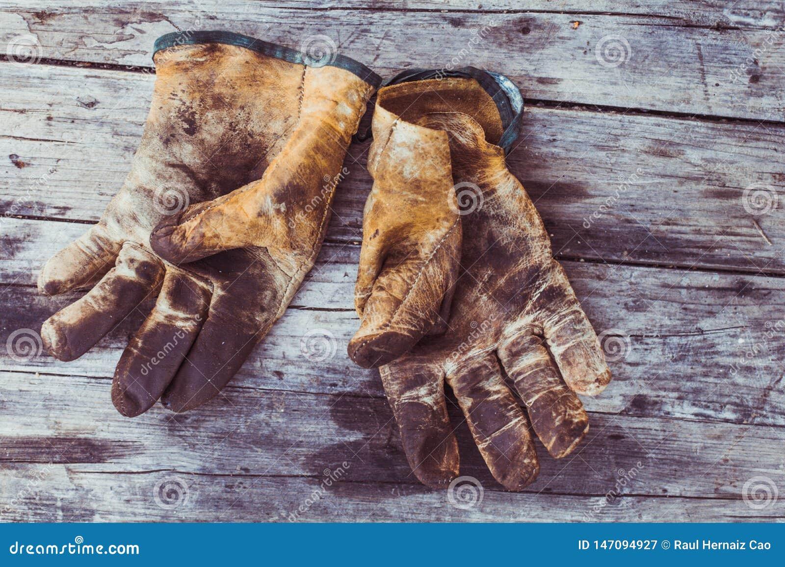 Odgórny widok stary wieśniak i brudne pracujące rękawiczki nad drewnianym stołem, rękawiczki dla each dotyka