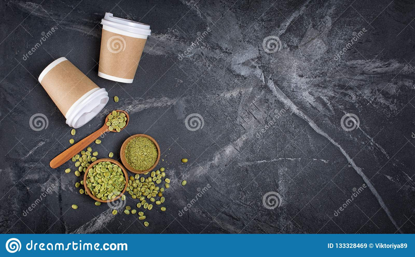 Odgórny widok surowe zielone unroasted zmielone kawowe fasole w drewnianych pucharach i łyżce z rozporządzalnym za filiżankach