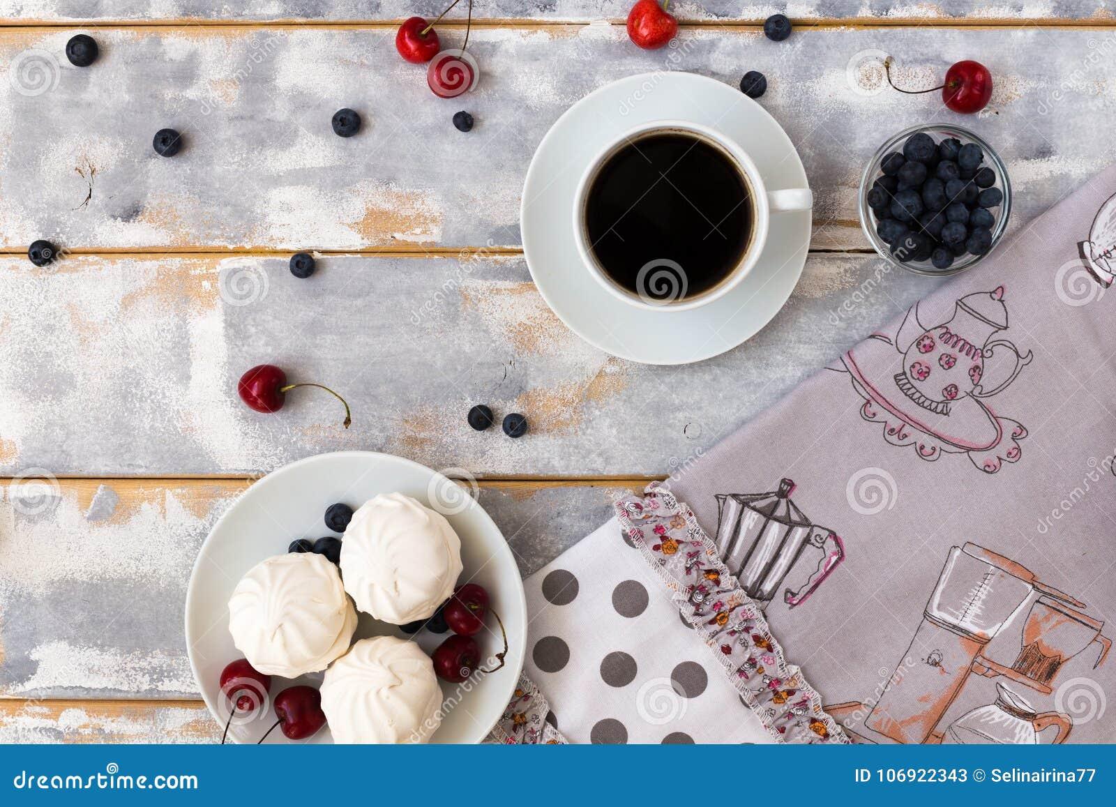 Odgórny widok wyśmienicie śniadanie z croissants, kawa, czarne jagody i wiśnia na stole,