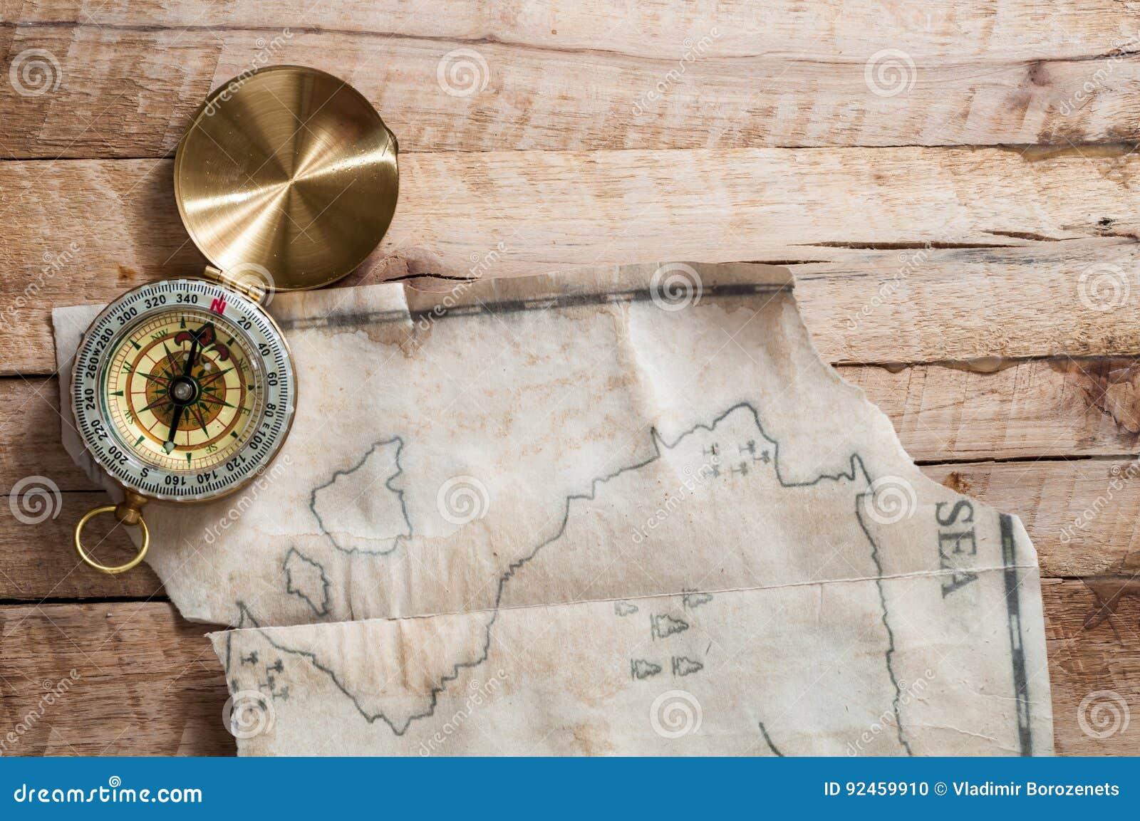 Odgórny widok złocisty kompas na drewnianym biurku z sfałszowaną handmade rocznik mapą