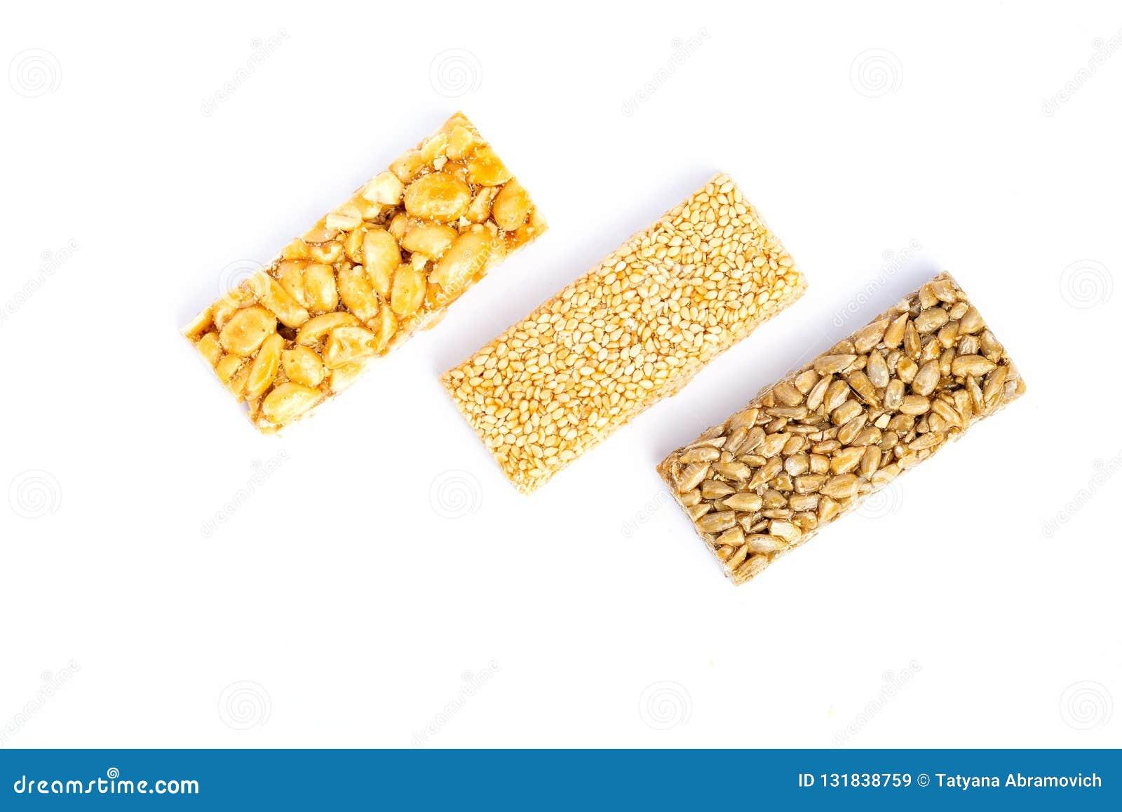 Odizolowywający nad biel prętowy tła granola Zdrowa słodka deserowa przekąska Sezam, hazelnut, słonecznik w miodzie Gozinaki jest