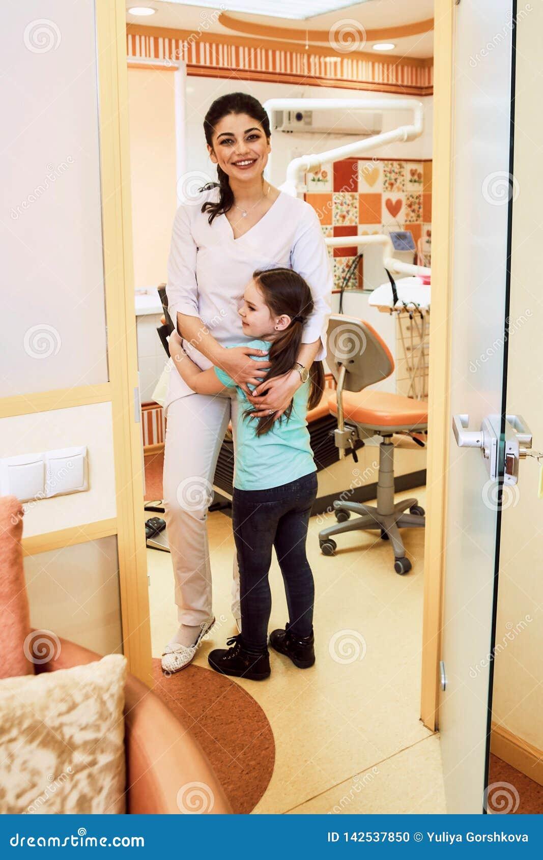 Odontologia pediatra A menina está feliz encontrar o dentista
