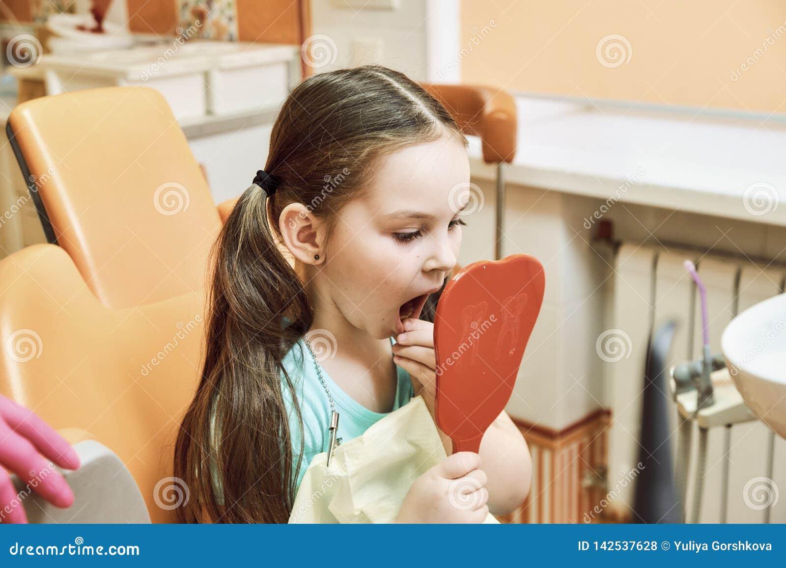 Odontologia pediatra A menina olha seus dentes no espelho
