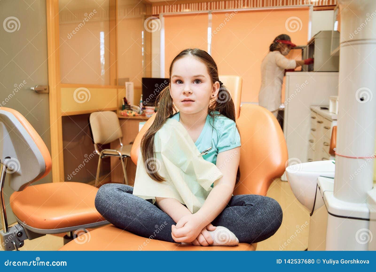 Odontologia pediatra Menina que senta-se em uma cadeira dental