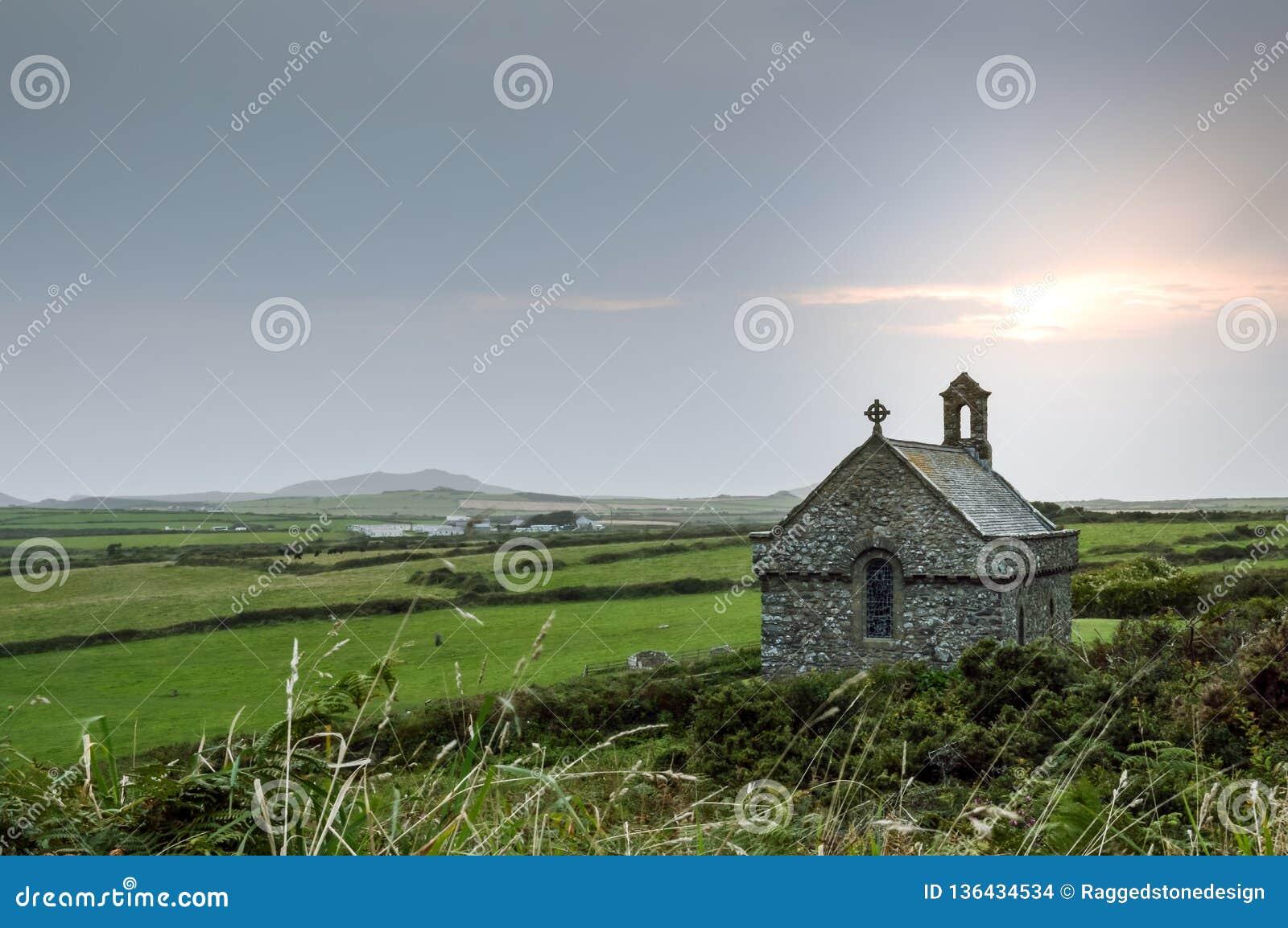 Odosobniona St Non kaplica z słońca położeniem za nim w Pembrokeshire, Walia