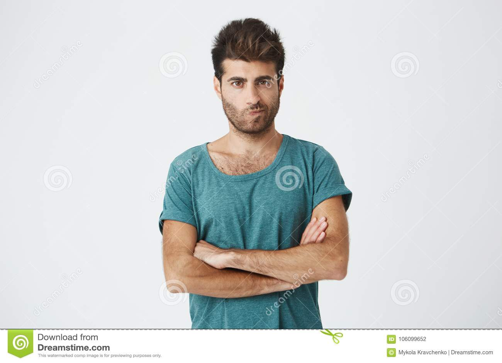 Odosobniony strzał jest ubranym błękitną koszulkę z eleganckimi fryzury mienia rękami gniewny mężczyzna krzyżował, mieć skeptical