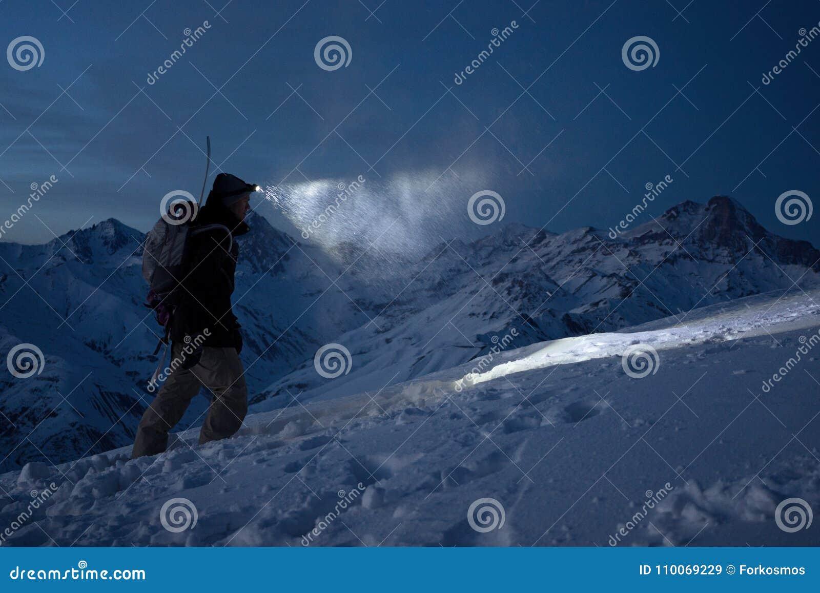 Odważny noc badacz wspina się na wysokich śnieżnych górach i zaświeca sposób z headlamp Krańcowa wyprawa Narciarska wycieczka tur