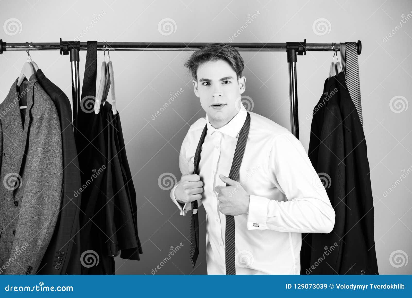Odziewa stojaka i mężczyzna w koszulowym jest ubranym krawacie na różowym tle