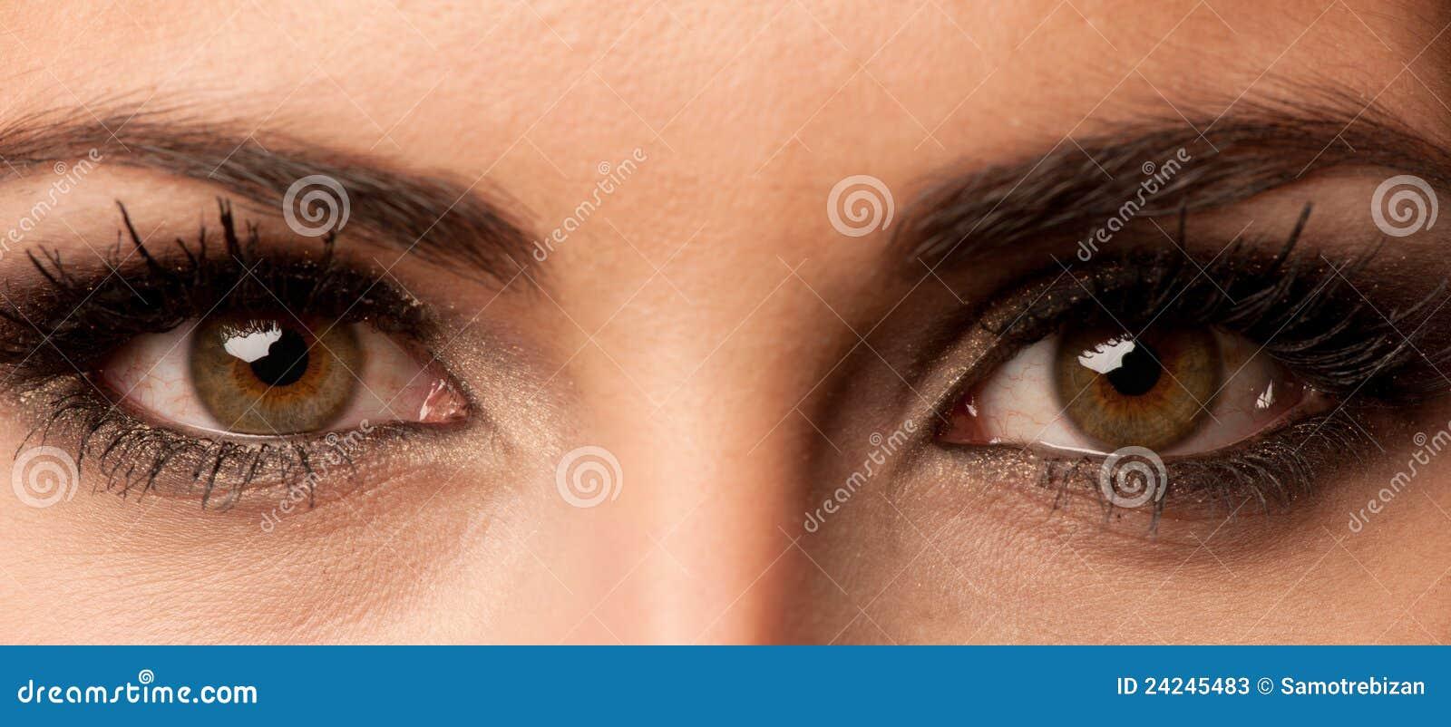 Oeil brun de femme avec le renivellement de couleur en pastel