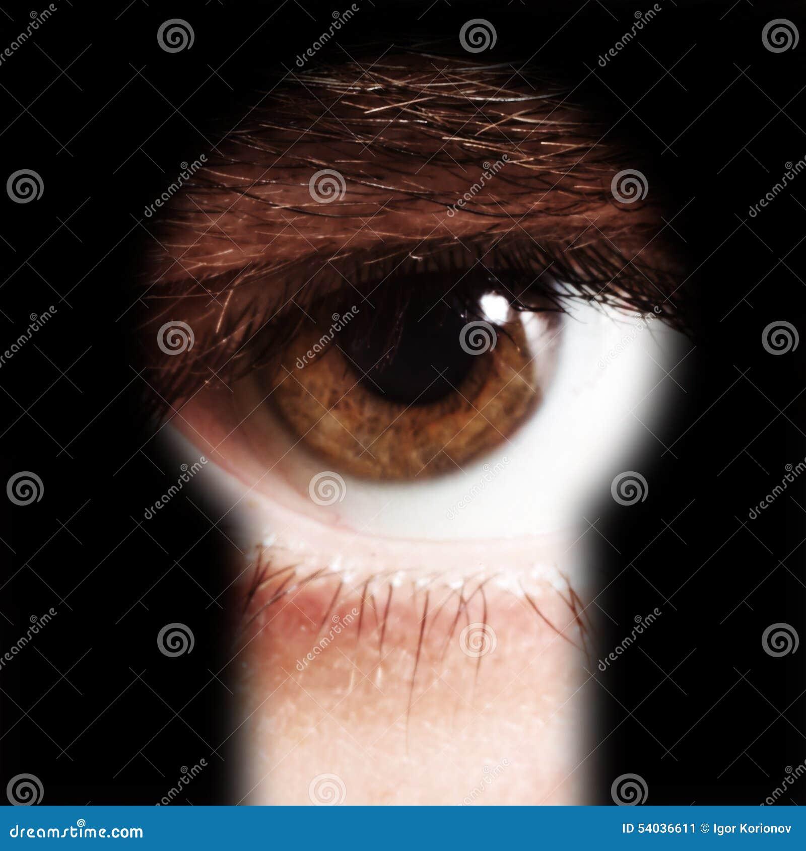 Oeil masculin remarquant par un trou de la serrure