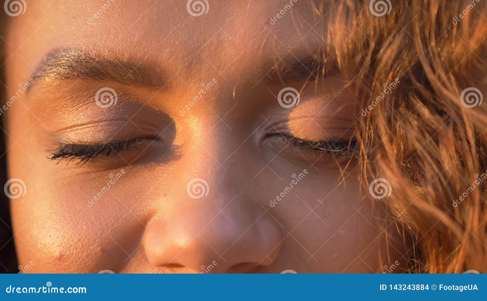 Oeil-portrait en gros plan de fille caucasienne assez aux cheveux bouclés avec les yeux fermés