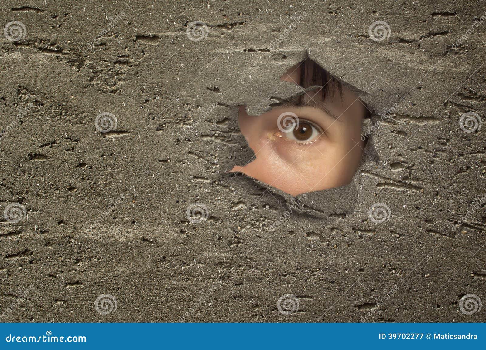 Oeil regardant par un trou dans le mur.