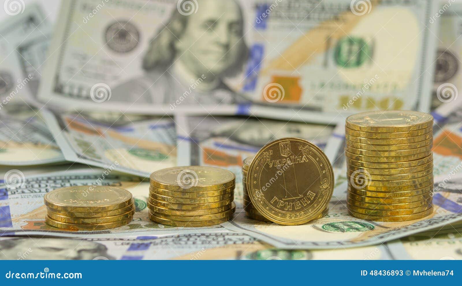 Oekraïense muntgrivna (hryvnia, 1 UAH) op de achtergrond van de rekeningen van de 100 dollarsv.s. (100 USD)