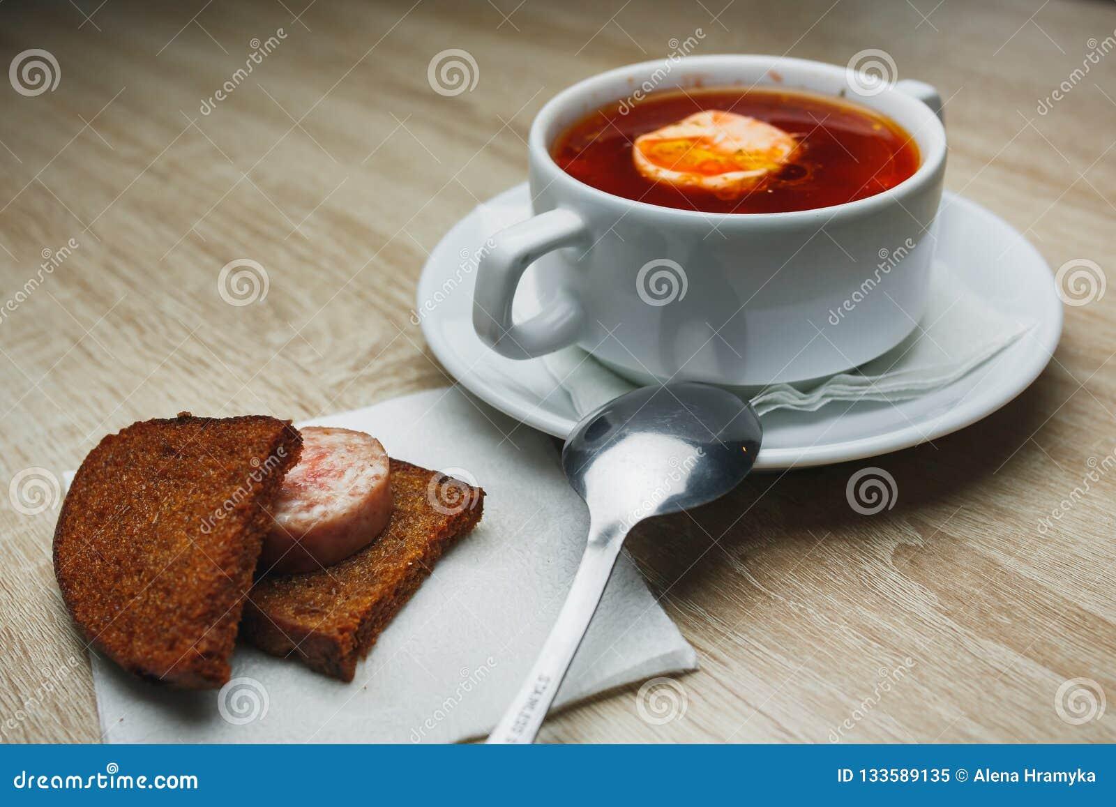 Oekraïense traditionele borsjt Russische vegetarische rode soep in witte kom op rode houten achtergrond Hoogste mening Borscht, b
