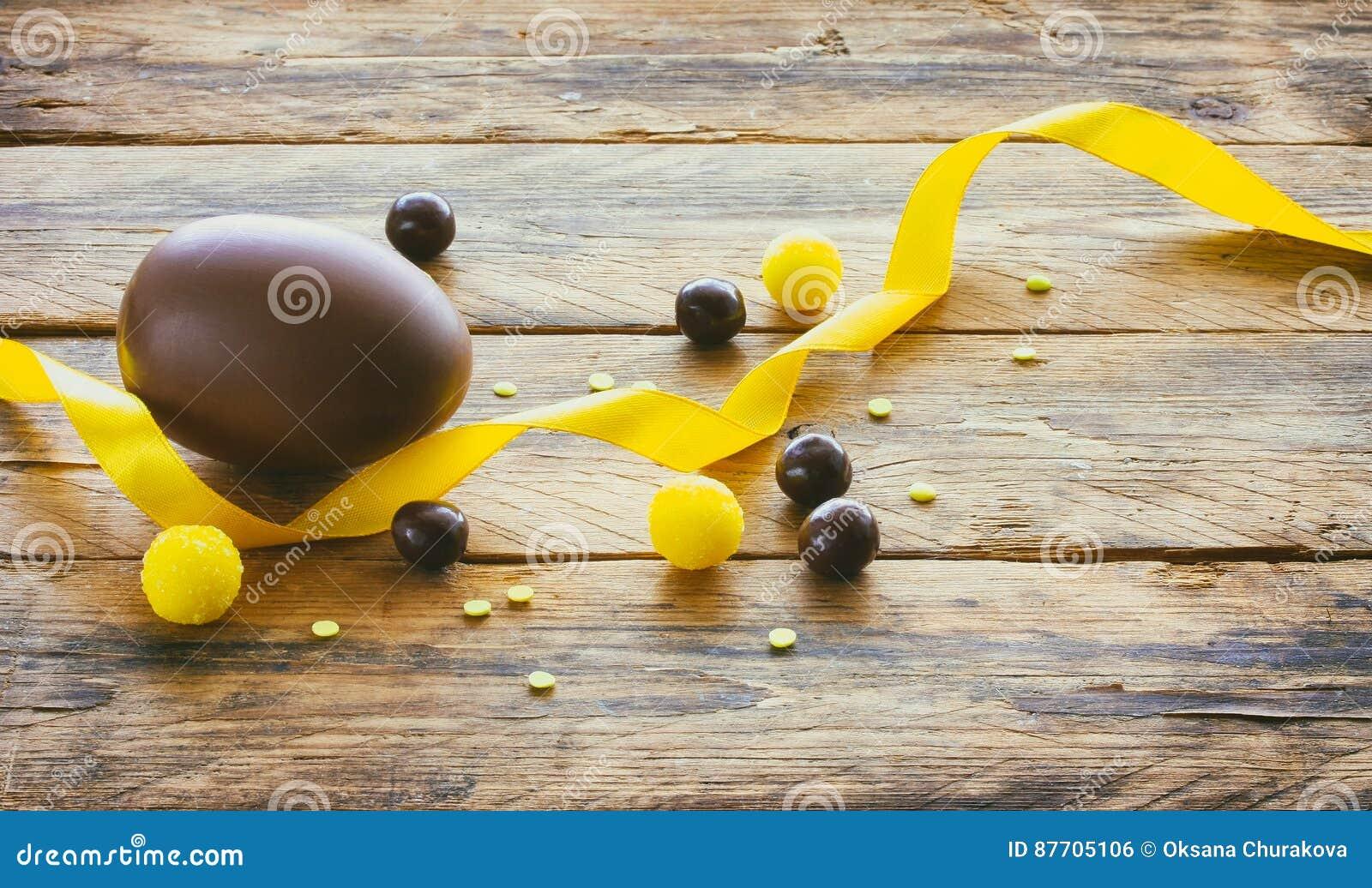 Oeuf de chocolat de Pâques, dragées de sucrerie, ruban en soie jaune
