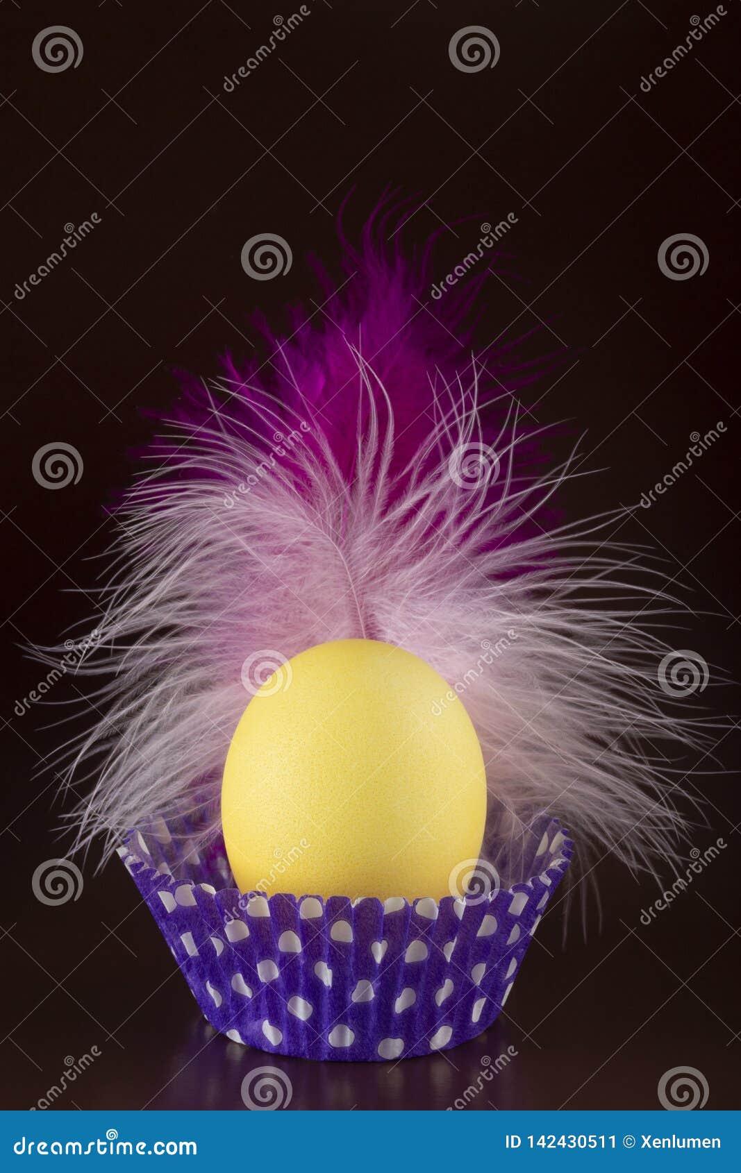 Oeuf de tyellow de Pâques avec une belle plume rose